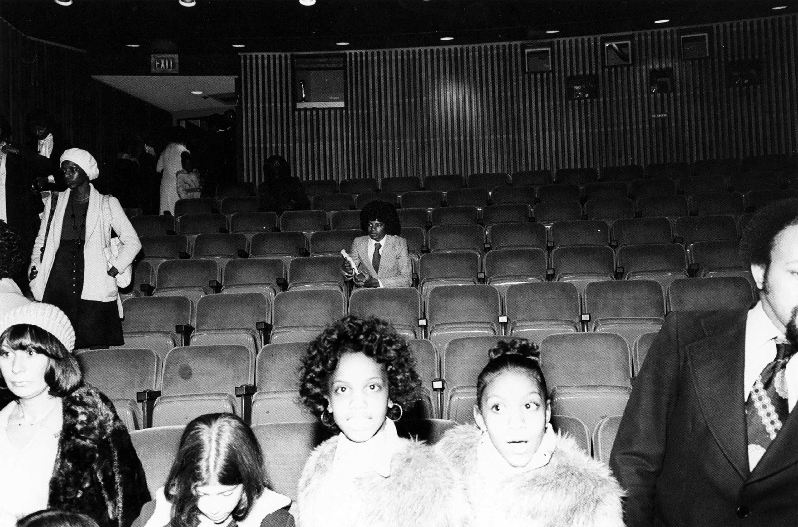 Michael Jackson sits alone in a movie theater in New York City in the 1970s.