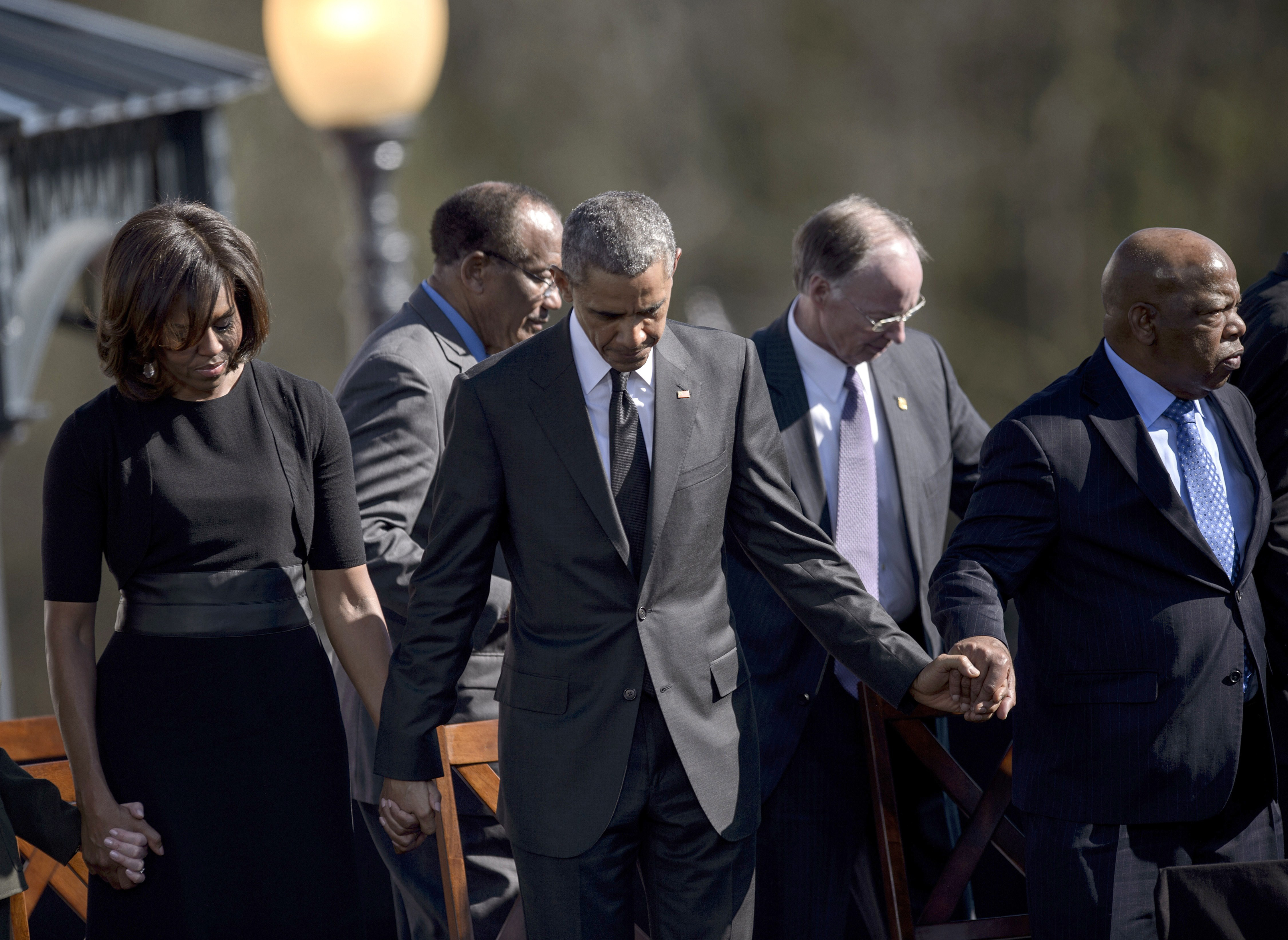 First Lady Michelle Obama, US President Barack Obama, Robert J. Bentley and US Representative John Lewis bow their heads for a prayer at the Edmund Pettus Bridge in Selma, Alabama, on March 7, 2015.