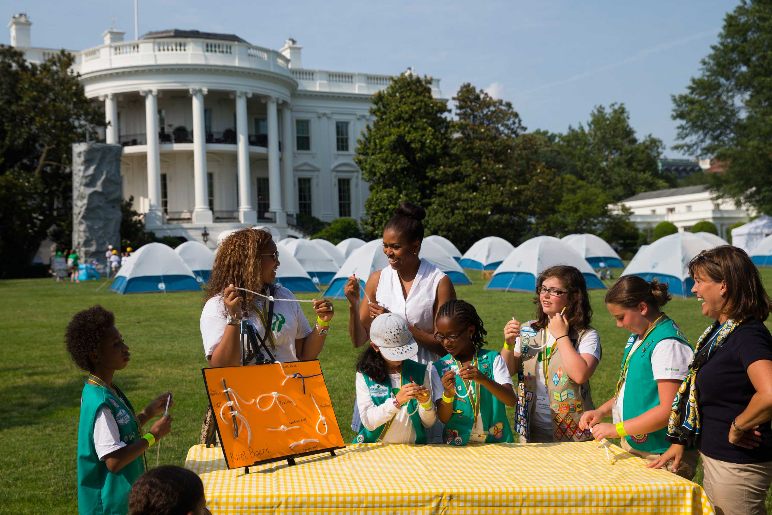 First lady Michelle Obama participates in a knot tying station during a Lets Move! event with Girl Scouts on the South Lawn of the White House in Washington, on June 30, 2015.