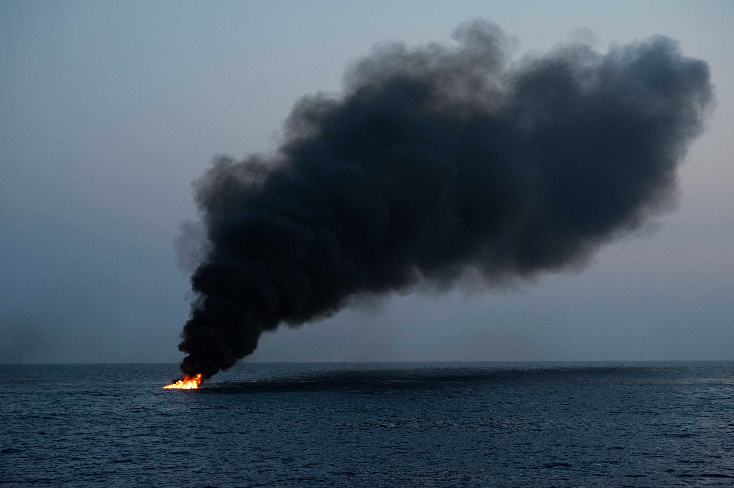 Smoke billows from a migrant boat, set ablaze by Italian authorities so other smugglers don't use it, after they rescued more than 100 people some 120 miles off the Italian coast on June 6, 2015.