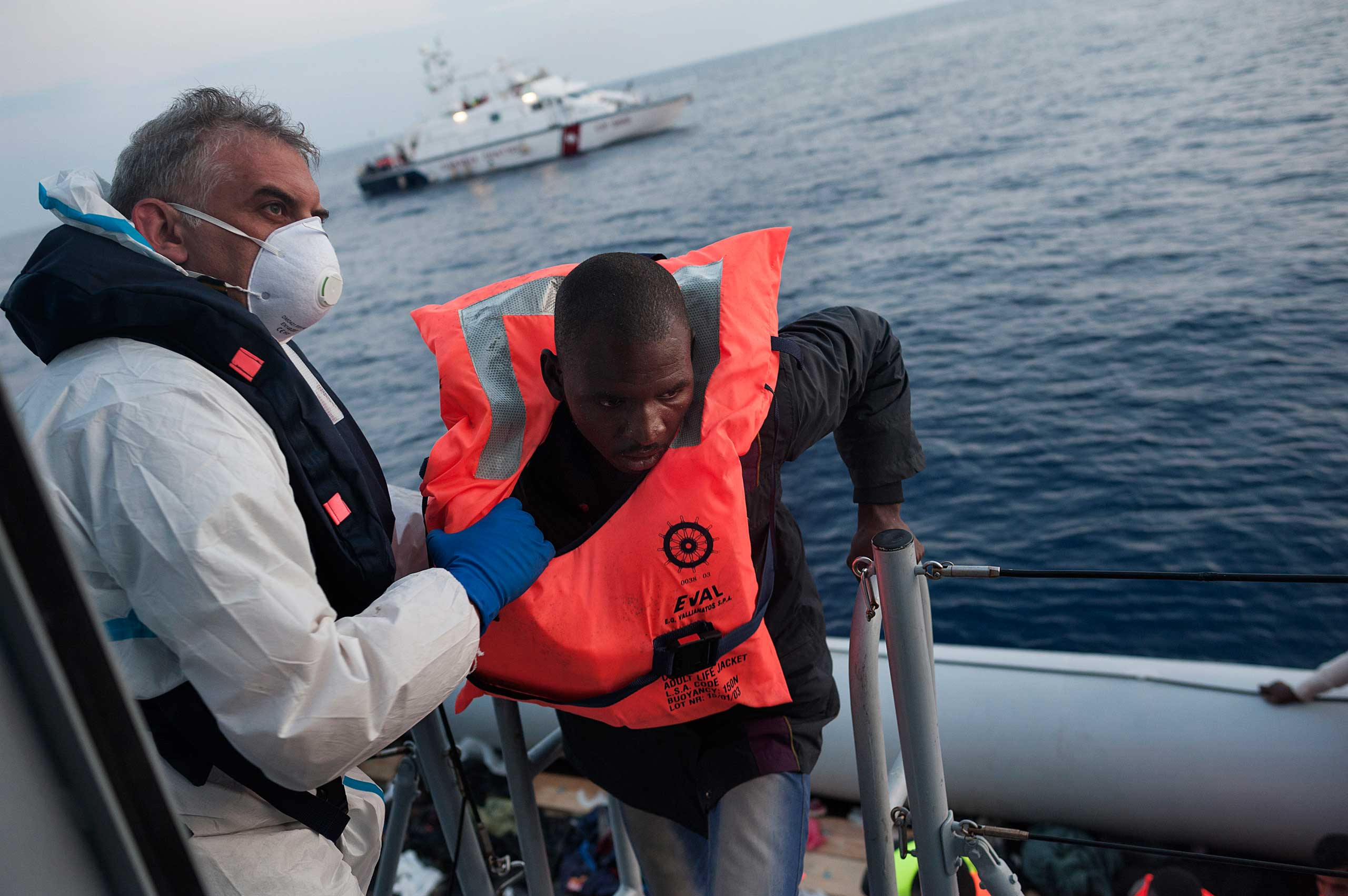 A member of Italy's Guardia di Finanza brings a migrant aboard after they were rescued from an inflatable boat, which originated in Libya and was found some 120 miles off the Italian coast in the Mediterranean, on June 6, 2015.