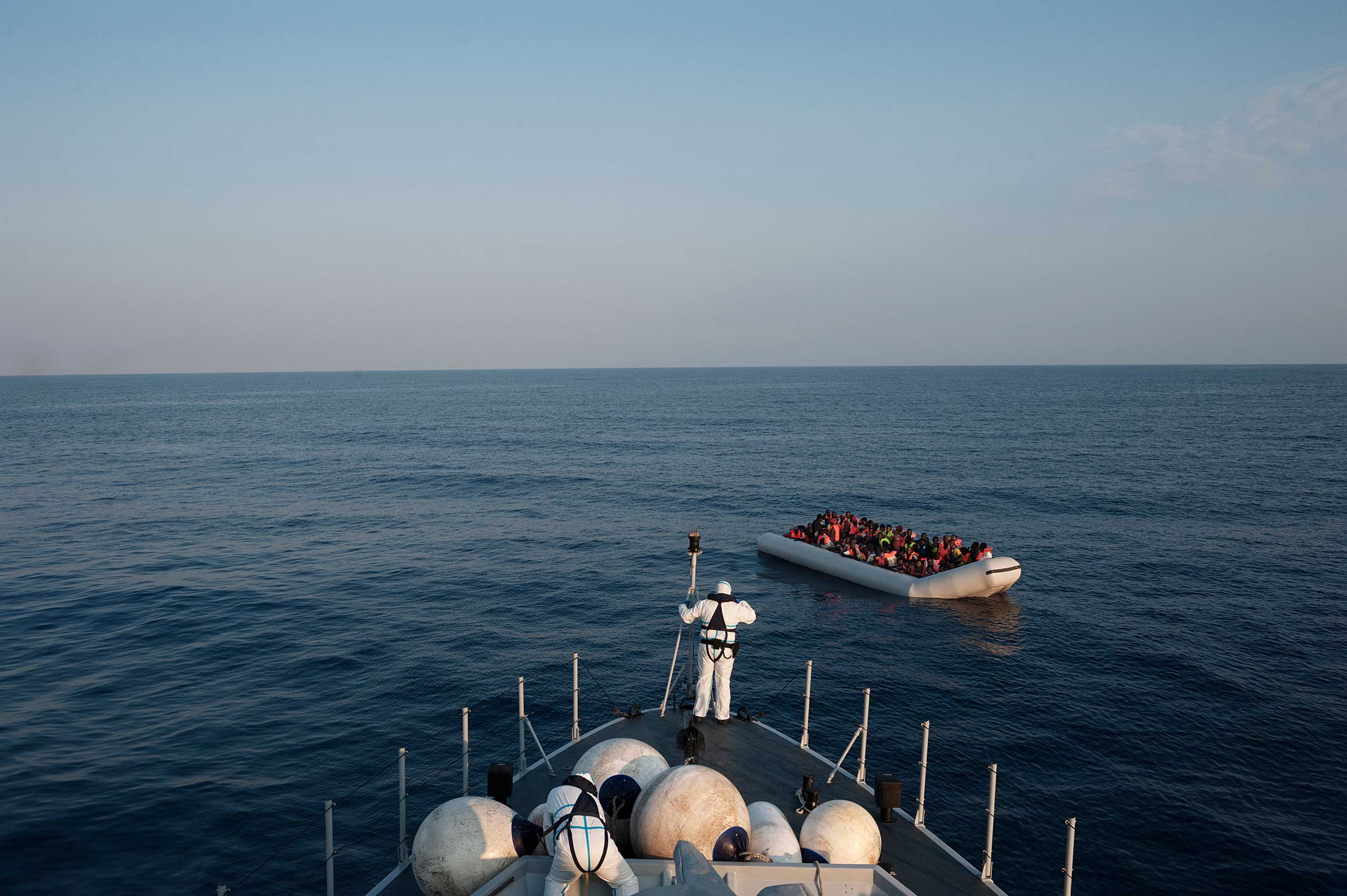 A ship belonging to Italian authorities approaches one of three migrant rafts some 120 miles off the Italian coast, about 40 miles from Libya, on June 6, 2015.