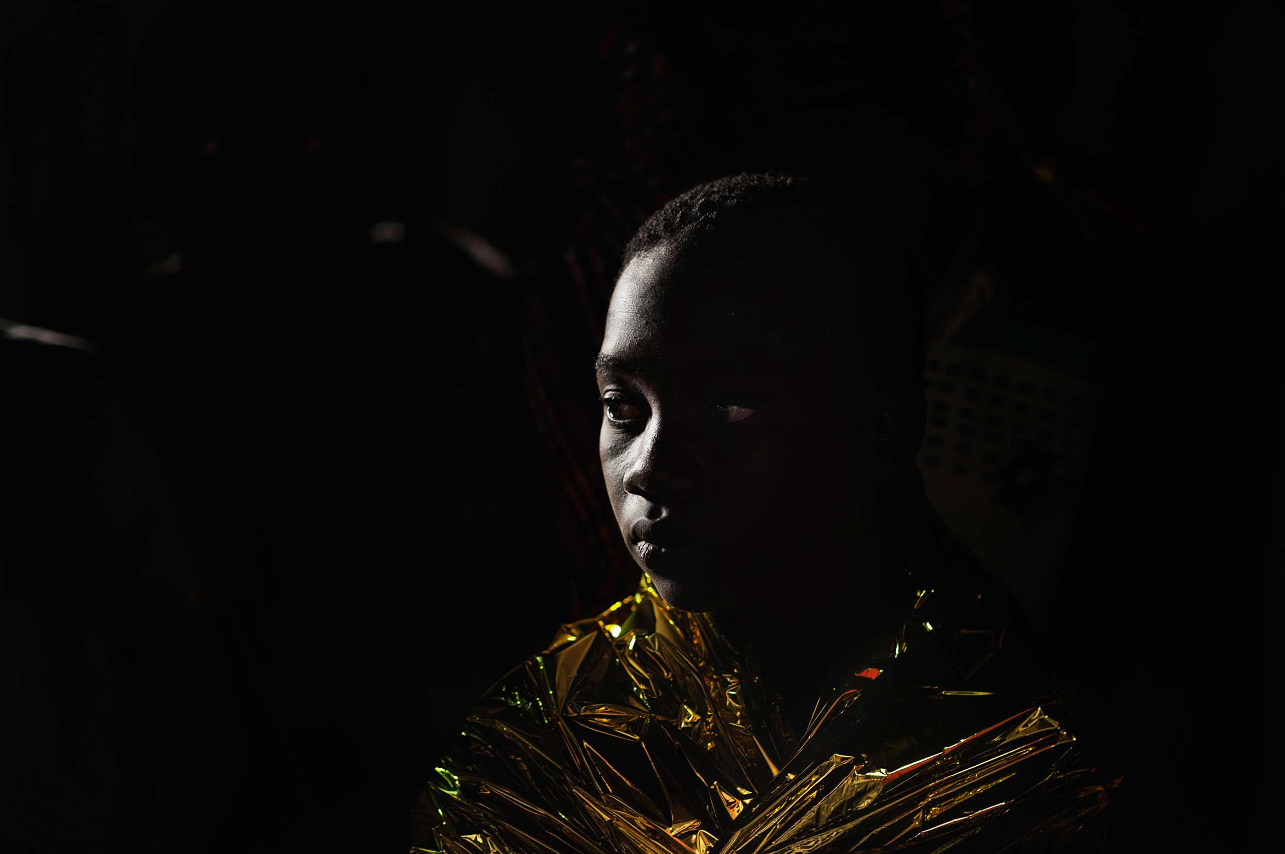 An African boy stands covered with a thermal sheet in Lampedusa after being rescued some 120 miles off the Italian coast on June 6, 2015.