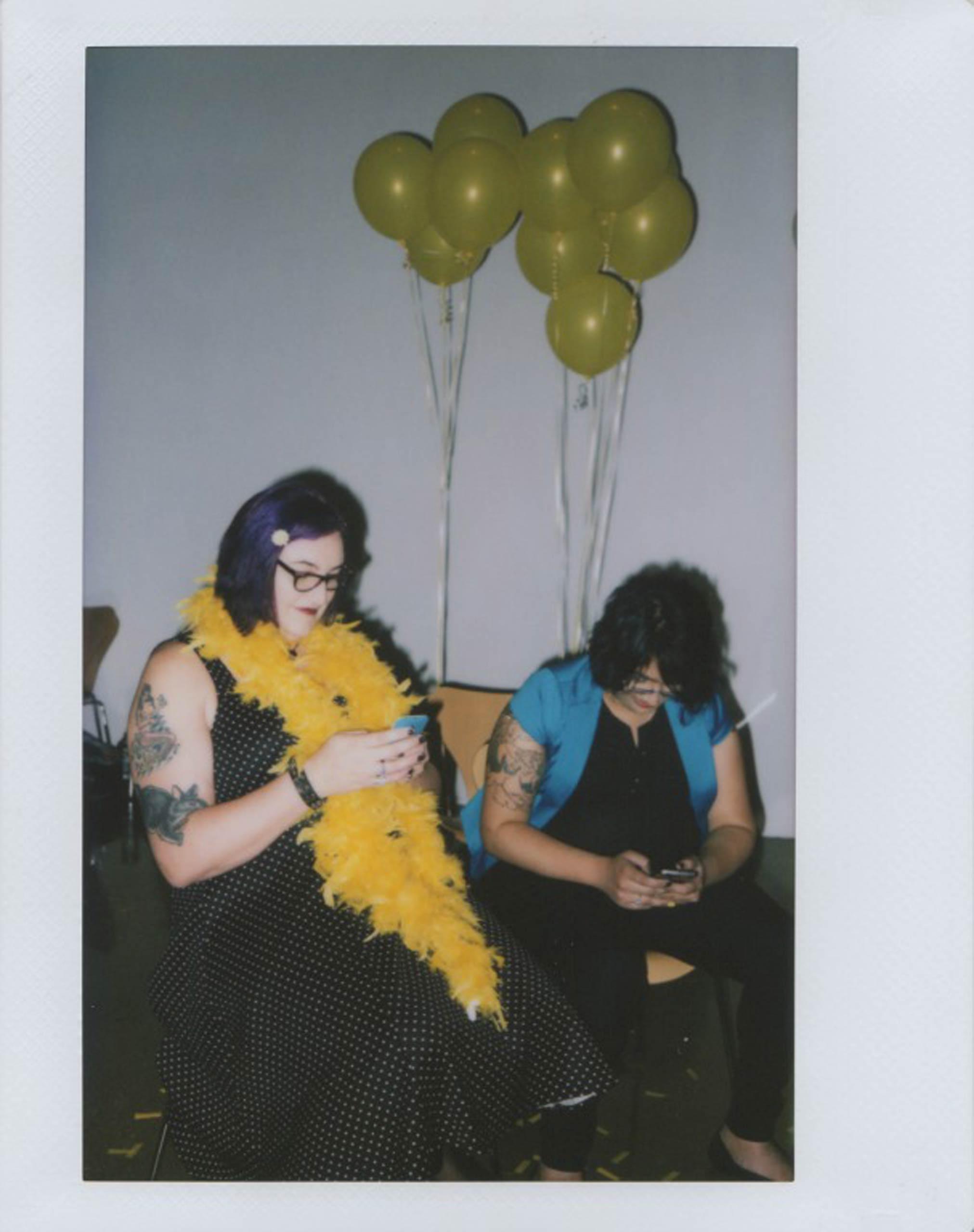 Greta Martela, left, and Nina Chaubal check their phones at the #InstaPride photo shoot in Hollywood, Calif., on May 22, 2015.