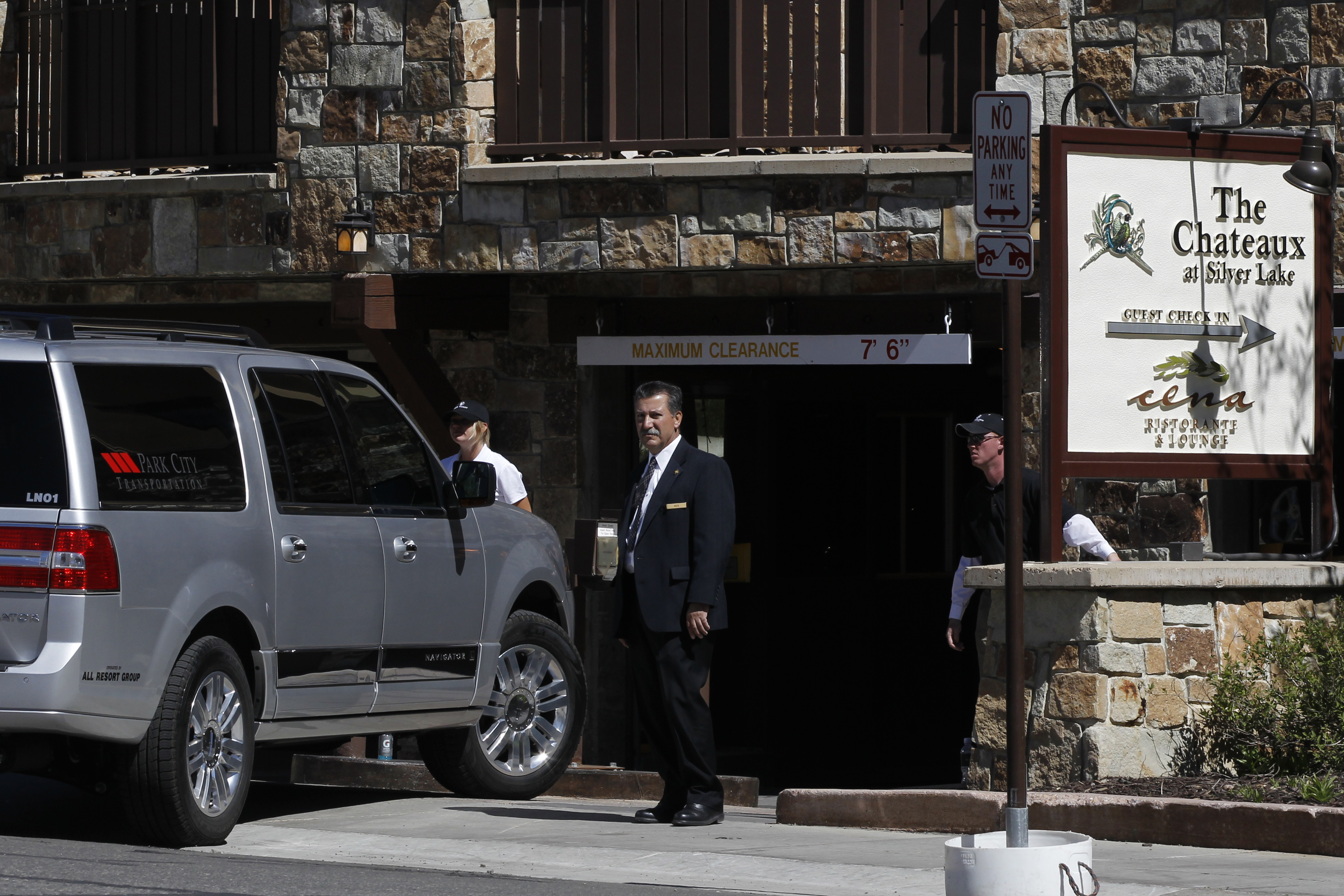 Security officials stand watch as cars enter a garage at a private 2012 donors' conference for Republican presidential candidate Mitt Romney at The Chateaux at Silver Lake at Deer Valley Resort in Park City, Utah.