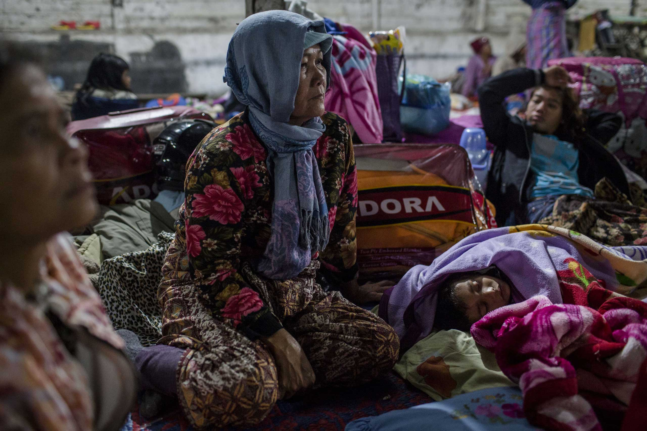Villagers rest inside a temporary shelter in Sukanalu village, North Sumatra, Indonesia  on June 16, 2015.
