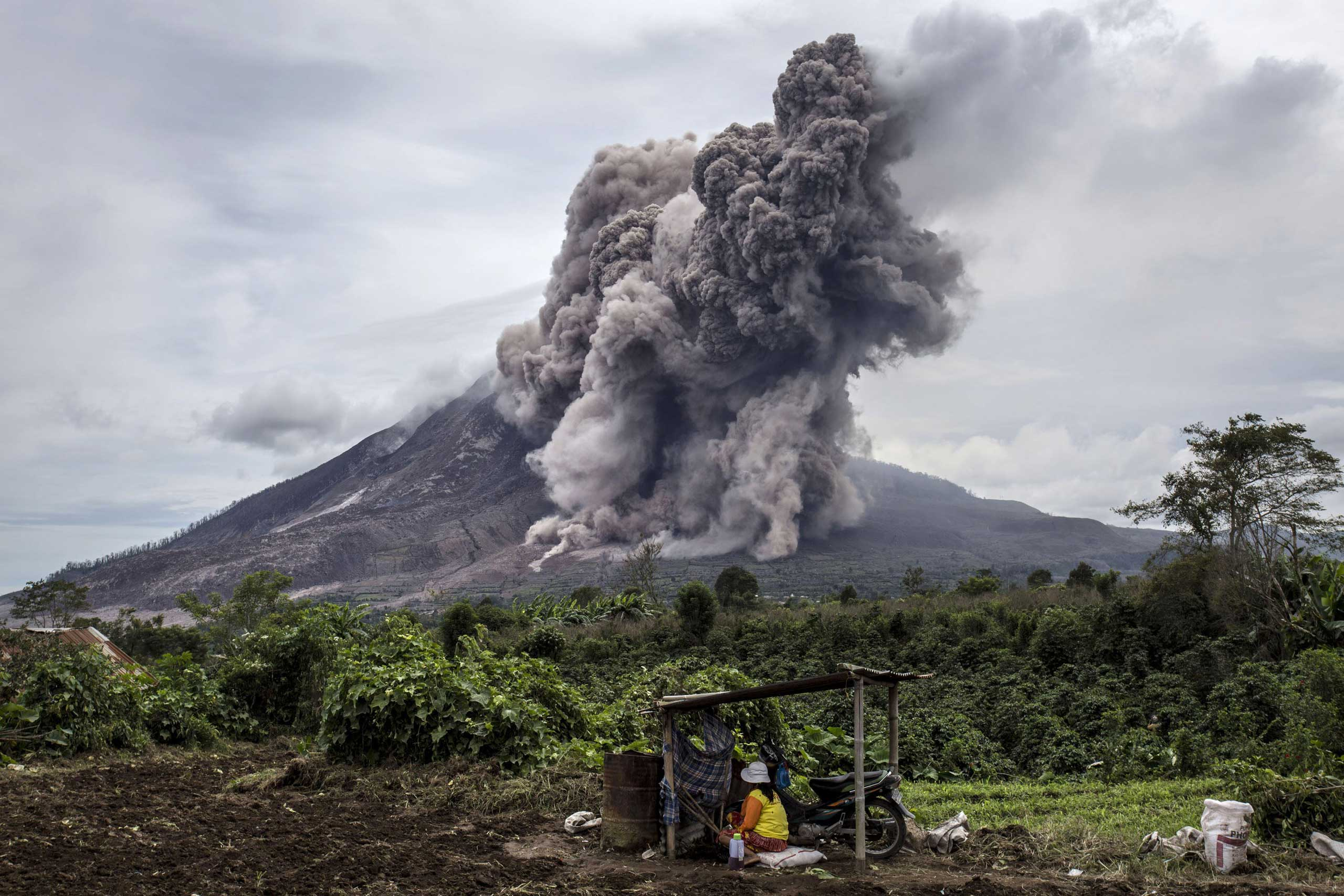 A local farmer sits on her fields as Mount Sinabung spews pyroclastic smoke, seen from Tiga Kicat village  in Sukanalu village, North Sumatra, Indonesia on June 17, 2015.