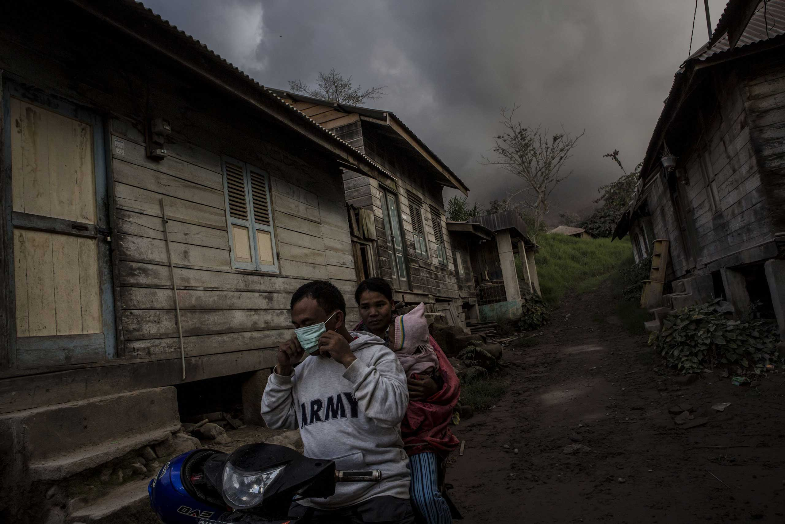 People on a motor cycle place masks on their faces as they flee their home to be evacuated to a temporary shelter in Sukanalu village, North Sumatra, Indonesia on June 16, 2015.