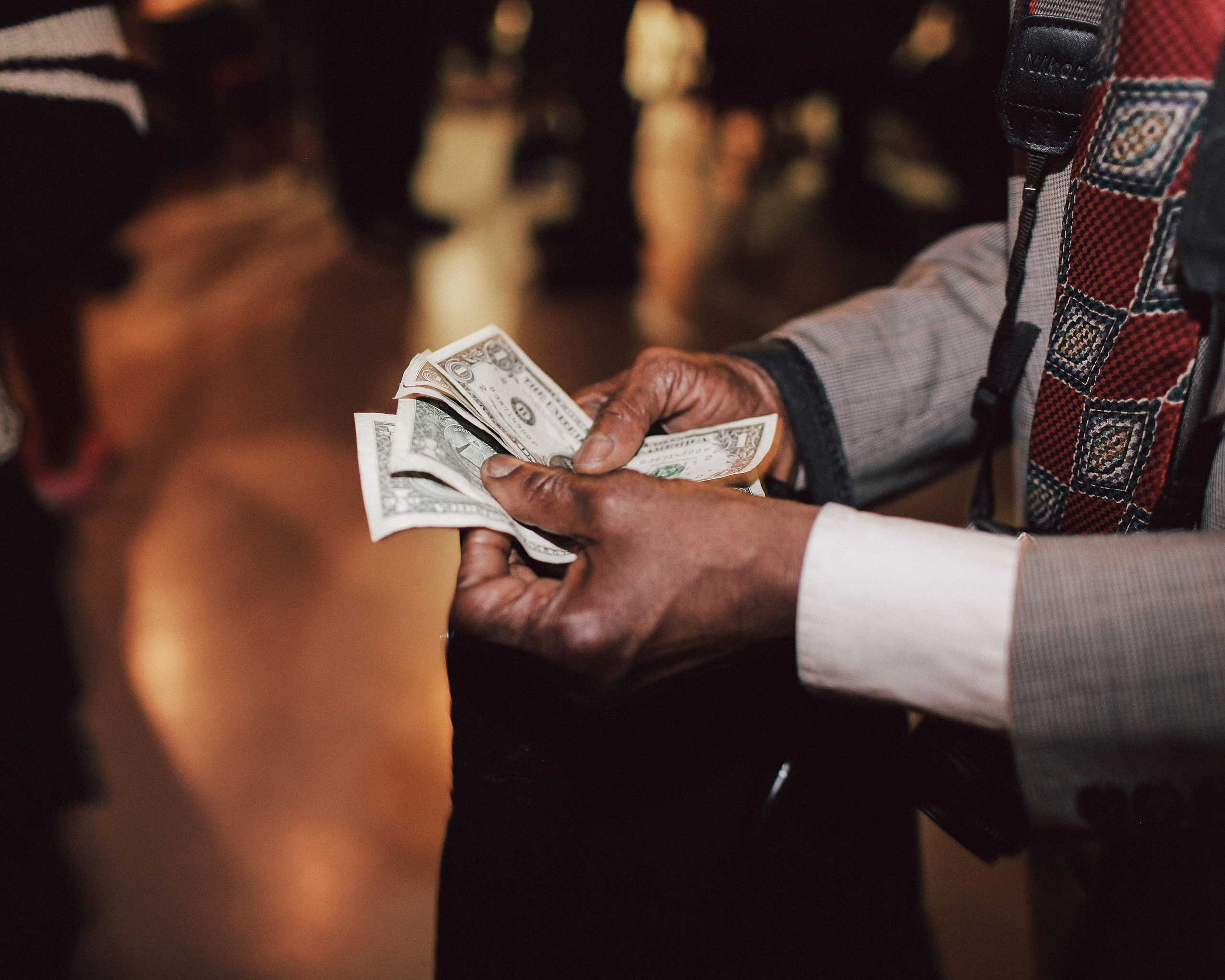 Alix Dejean counts his cash after sellings prints at a club in Harlem.