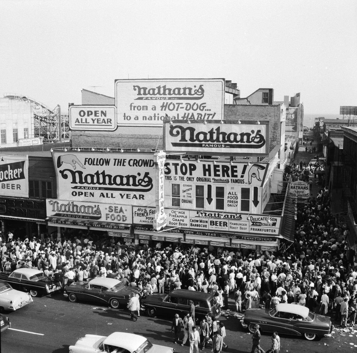 Crowds outside Nathan's Famous hot dog stand on Coney Island, New York City, circa 1955
