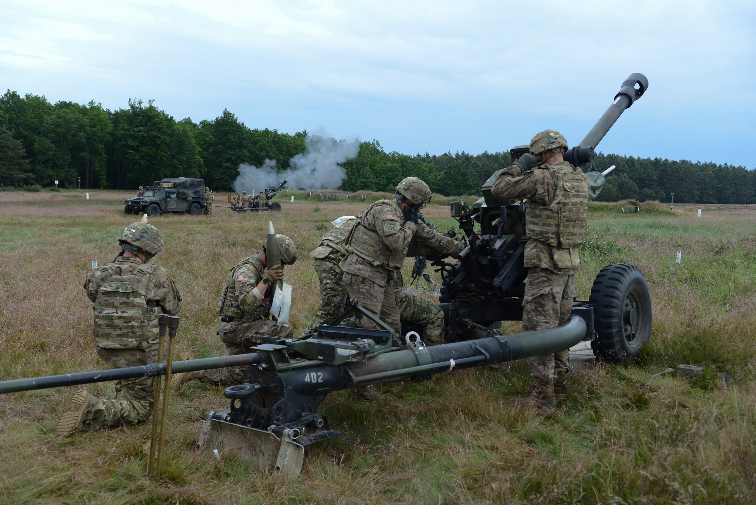 American soldiers with the 173rd Airborne load and fire an M119A3 howitzer at the Drawsko Pomorskie Training Area in Poland on June 18, 2015.