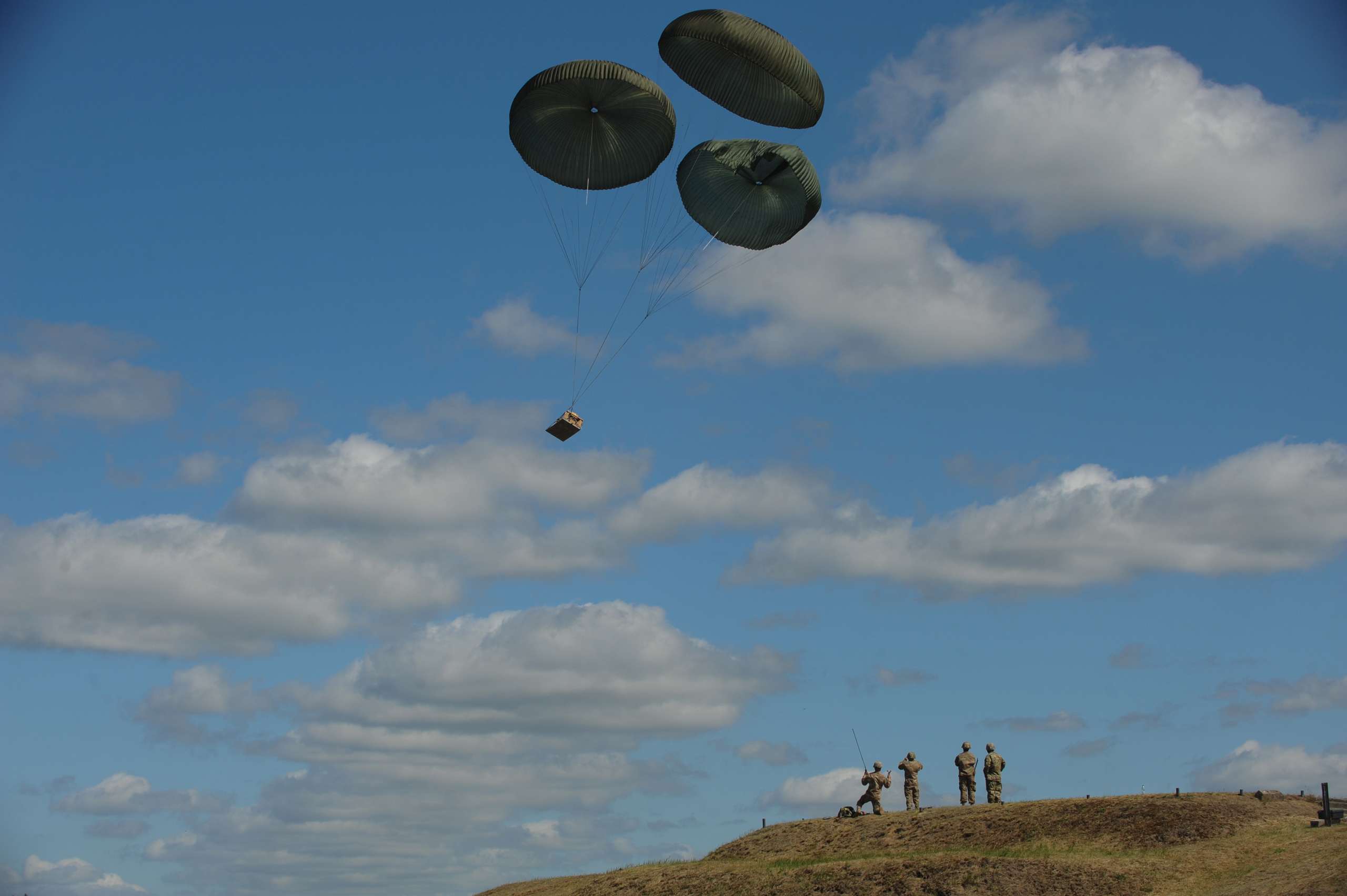 American soldiers from the Fourth of the 319th Airborne Field Artillery Regiment of the 173rd Infantry Brigade Combat Team monitor as a howitzer drops from a C-17 aircraft that took off from Nuremberg, Germany before American soldiers parachute to the ground at the Drawsko Pomorskie Training Area in Poland on June 15, 2015.