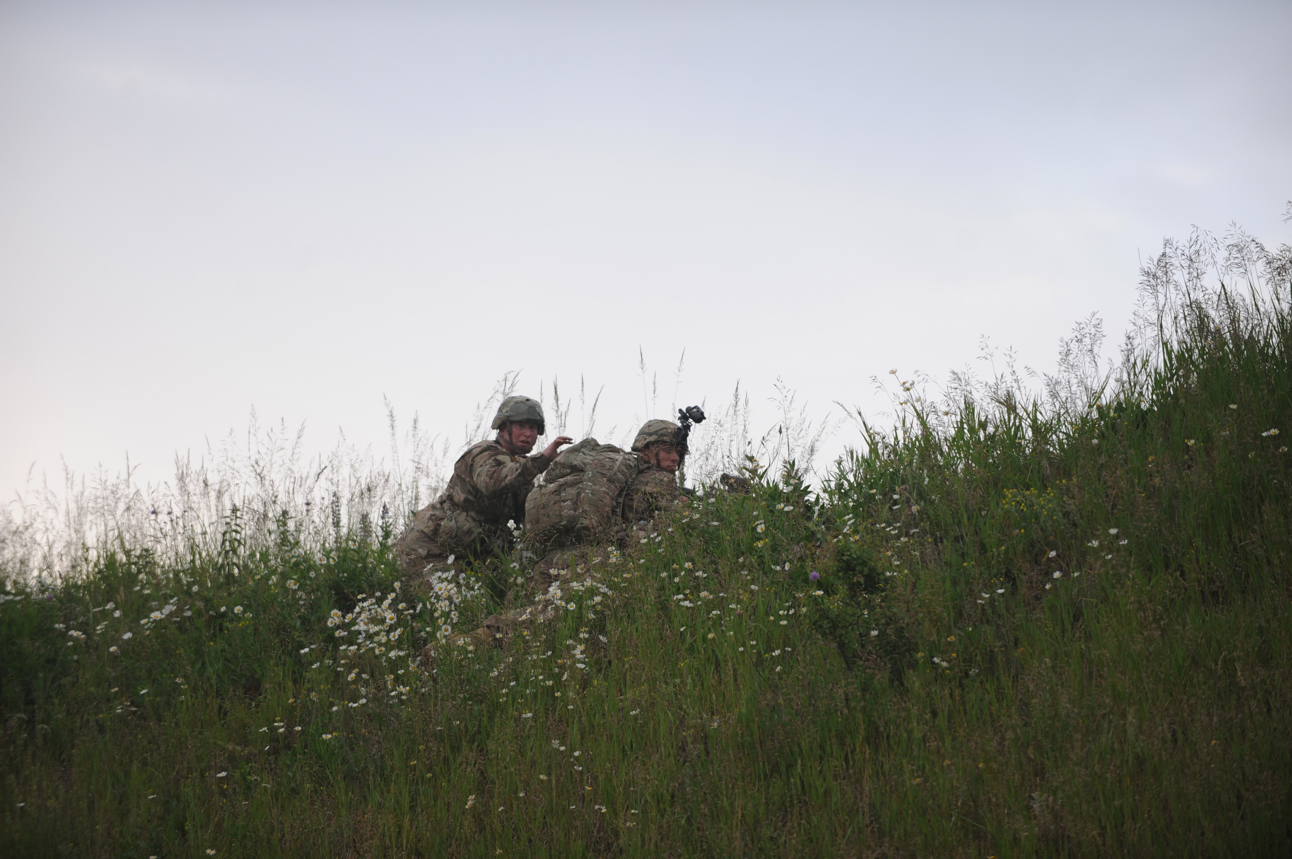 American soldiers with the 173rd Airborne, First Battalion, 503 Infantry Regiment maintain their position on a grassy knoll after parachuting in from a C-130 during an airfield seizure exercise on the Swidwin Airfield in Poland on June 16, 2015.