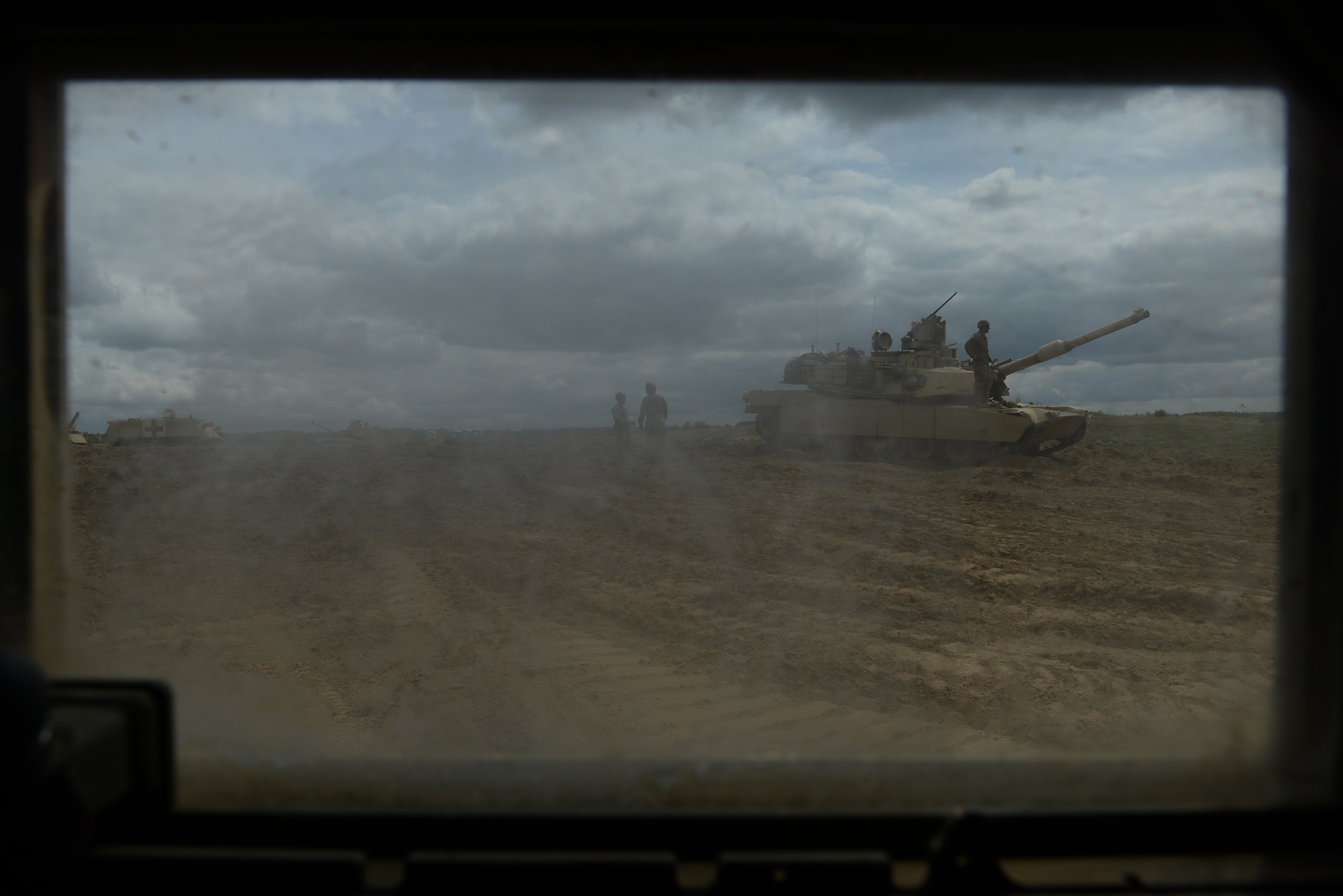 American soldiers with the Second Battalion, Seventh Infantry Regiment, Third Infantry Division based out of Fort Stewart, Georgia in an American Abrams M1A2 tank in position for a live fire exercise as seen through the window of a Humvee at the Drawsko Pomorskie Training Area in Poland on June 16, 2015.