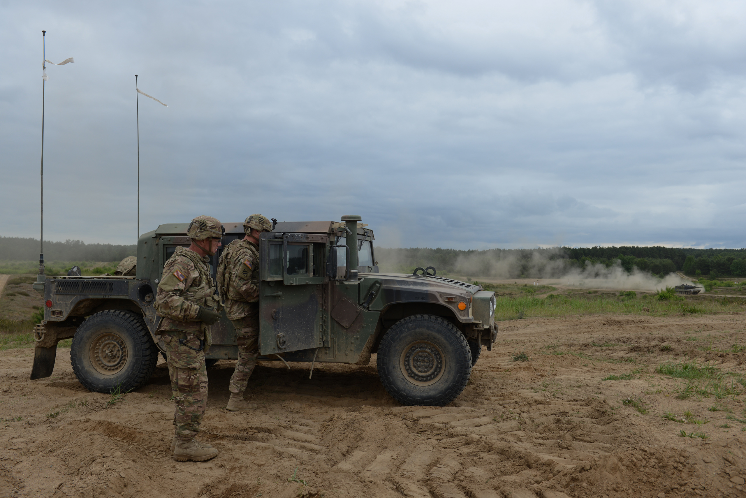 American soldiers with the  Second Battalion, Seventh Infantry Regiment, Third Infantry Division based out of Fort Stewart, Georgia beside a Humvee before a live fire exercise with a German-made Danish Leopard 2A5 tank on the horizon at the Drawsko Pomorskie Training Area in Poland on June 16, 2015.