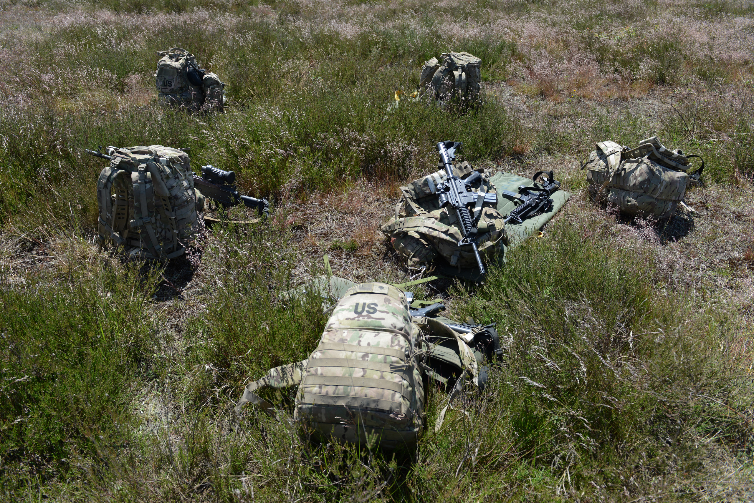Backpacks belonging to the paratroopers of the Fourth of the 319th Airborne Field Artillery Regiment of the 173rd Infantry Brigade Combat Team lay on the ground following an airdrop from a C-17 aircraft that took off from Nuremberg, Germany and dropped at the Drawsko Pomorskie Training Area in Poland on June 15, 2015.