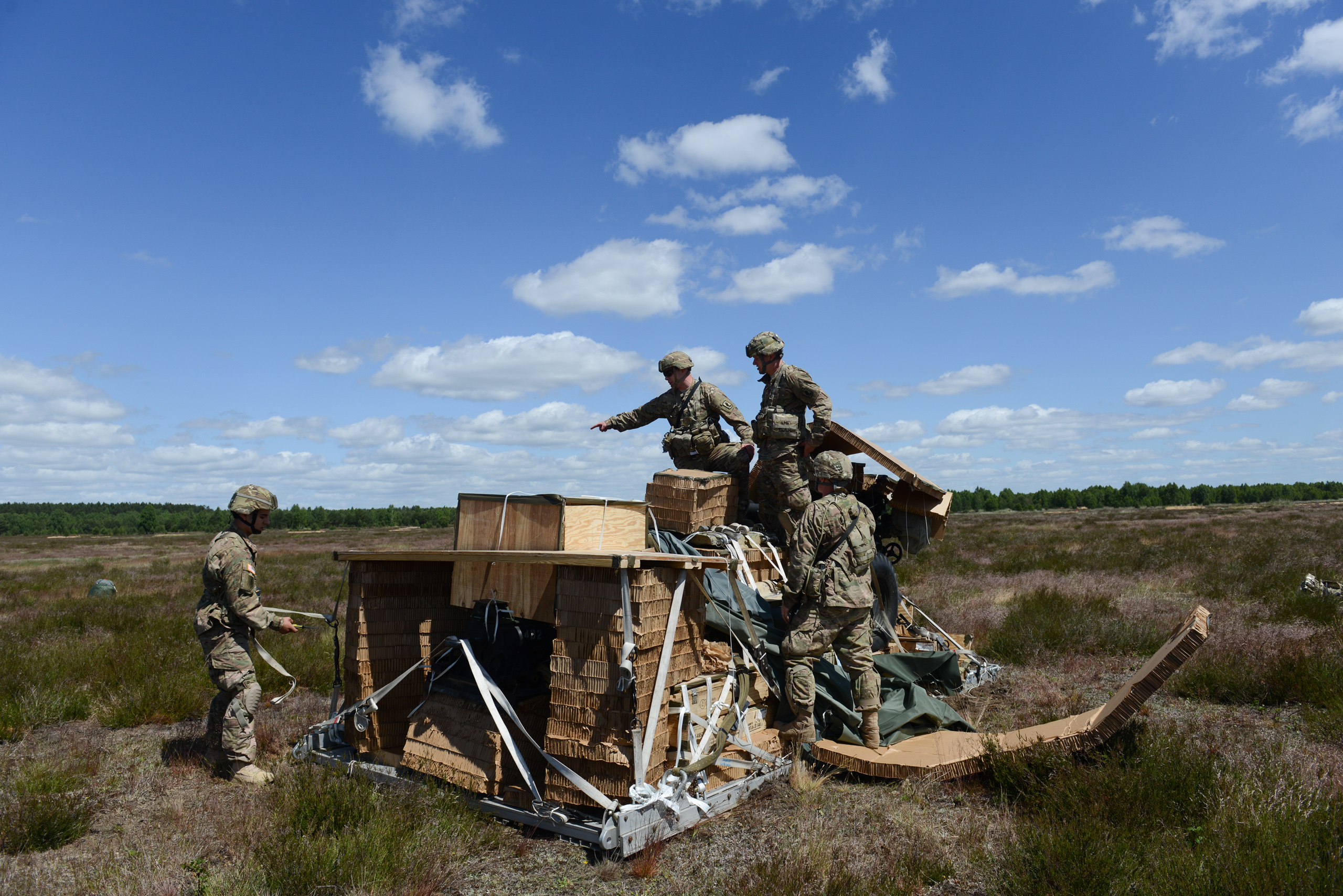 American soldiers with the Fourth of the 319th Airborne Field Artillery Regiment of the 173rd Infantry Brigade Combat Team proceed to assemble a howitzer following an airdrop from a C-17 aircraft that took off from Nuremberg, Germany and dropped at the Drawsko Pomorskie Training Area in Poland on June 15, 2015.