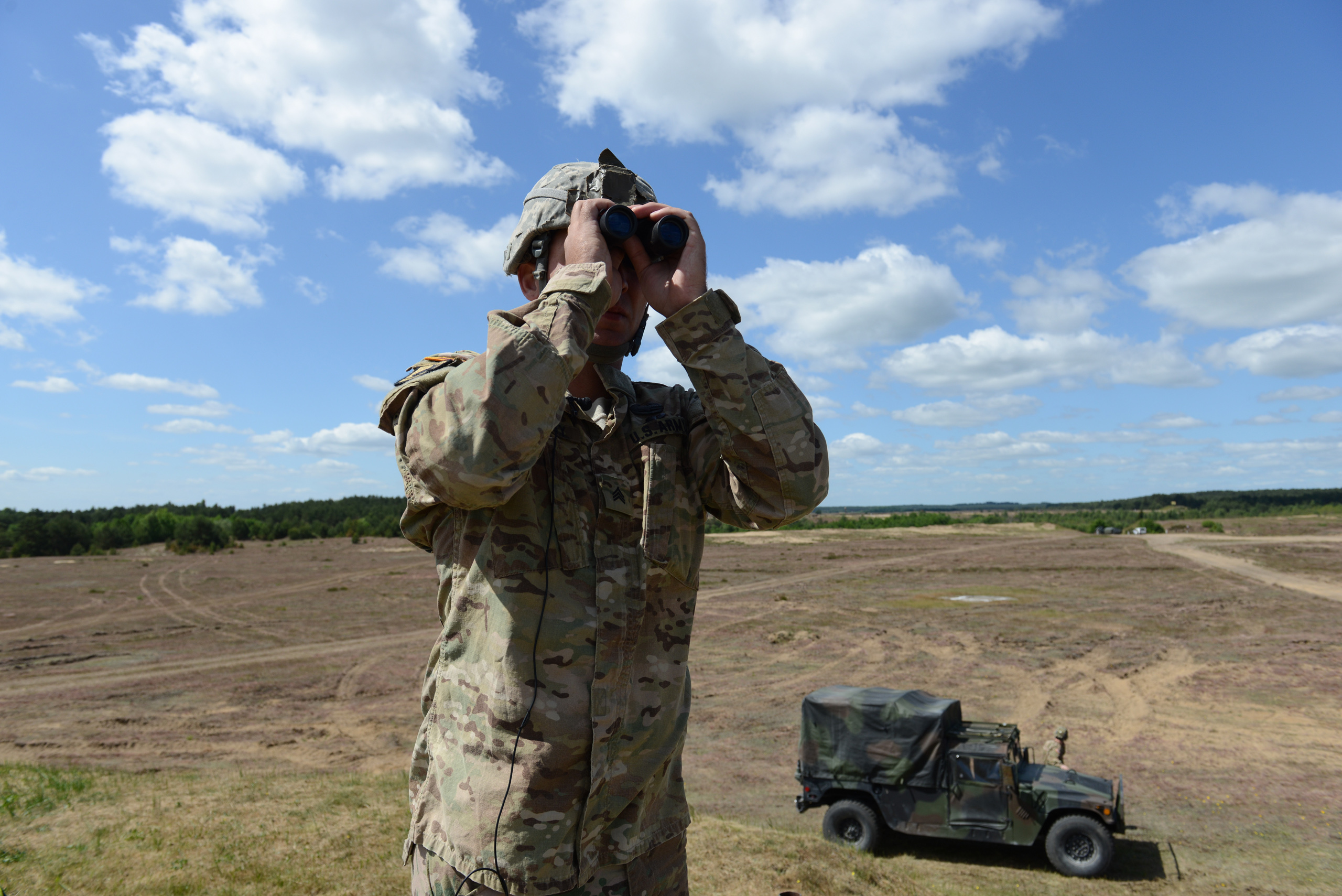 Sergeant Stephen Murphy with the Fourth of the 319th Airborne Field Artillery Regiment of the 173rd Infantry Brigade Combat Team monitors an airdrop from a C-17 aircraft that took off from Nuremberg, Germany before it drops members of his unit at the Drawsko Pomorskie Training Area in Poland on June 15, 2015.