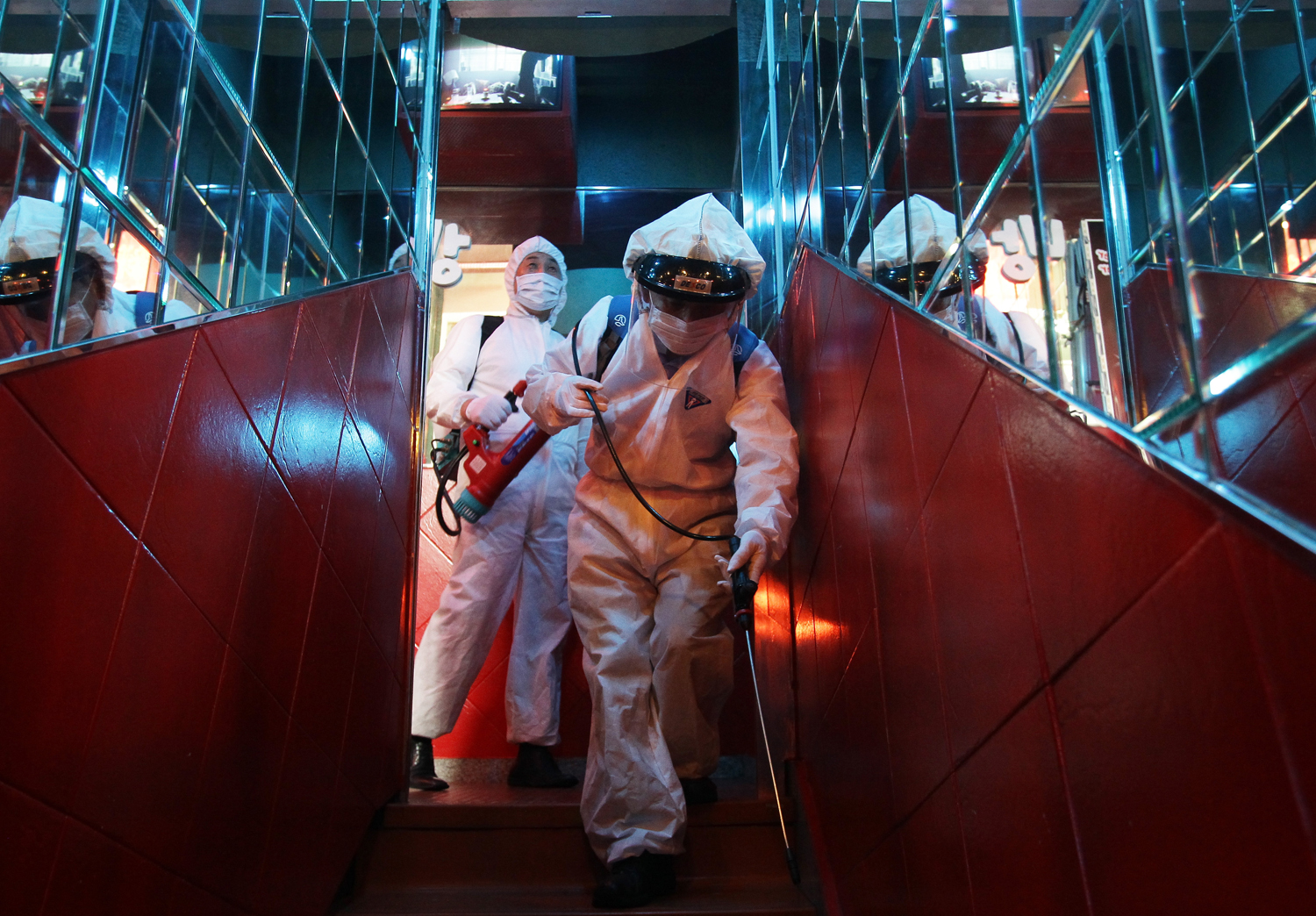 Disinfection workers wearing protective clothing spray anti-septic solution in a karaoke parlor on June 16, 2015 in Seoul, South Korea.