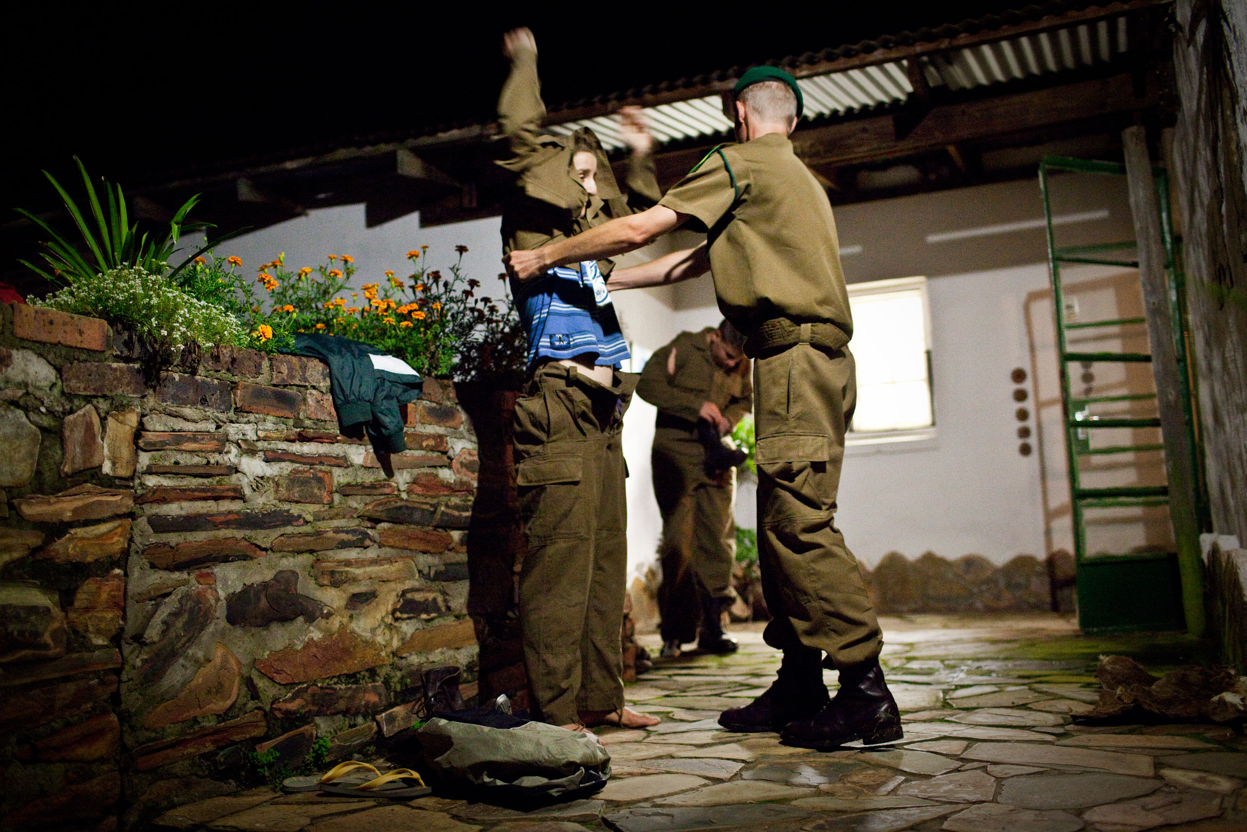 """One of the self-acclaimed sergeants at the camp helps one of the boys get dressed into old South African army uniforms, worn during apartheid. """"There are old blood stains on my uniform,"""" one of them says, as he trades his sneakers for army boots."""