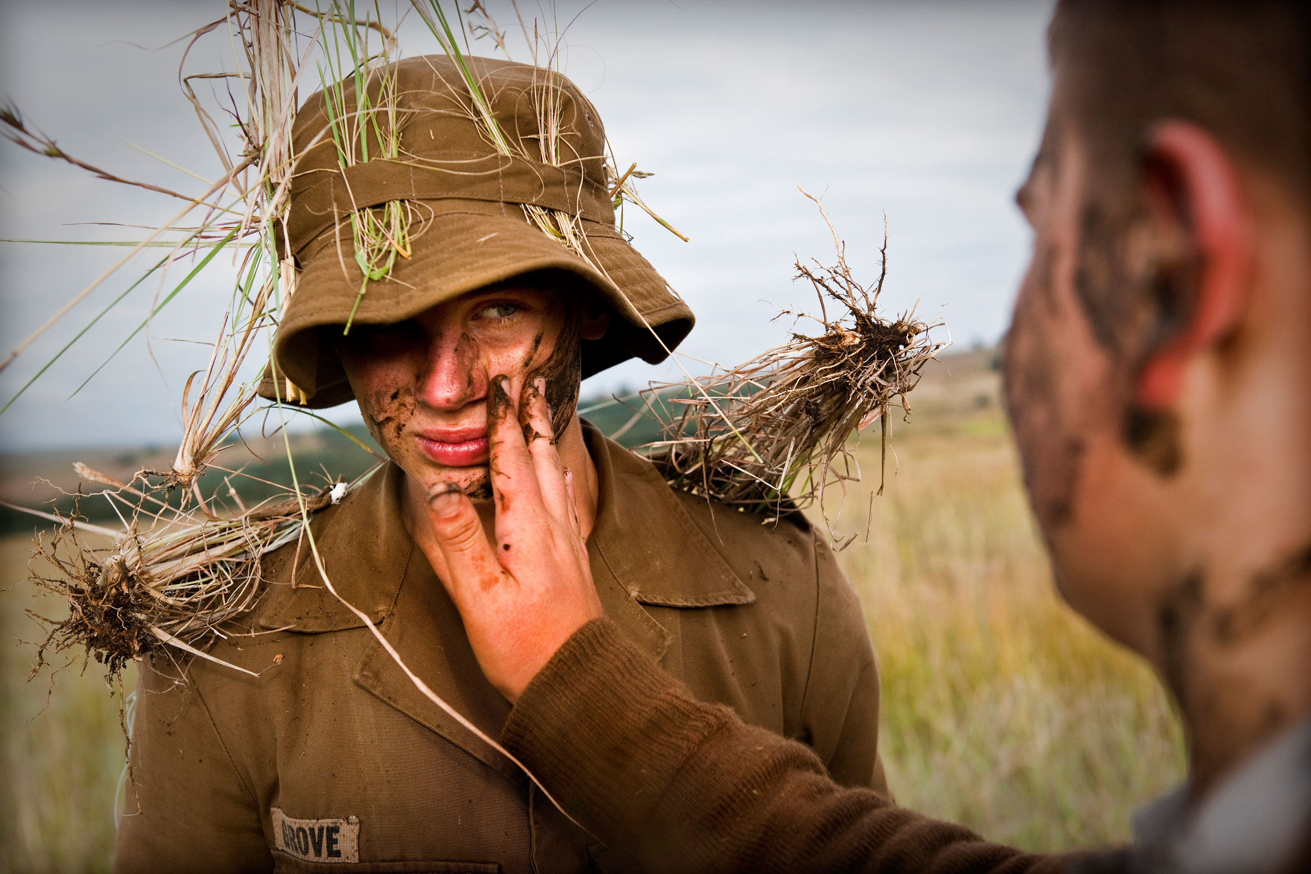 A boy puts mudd on another boy's face as camouflage during a nine day camp.