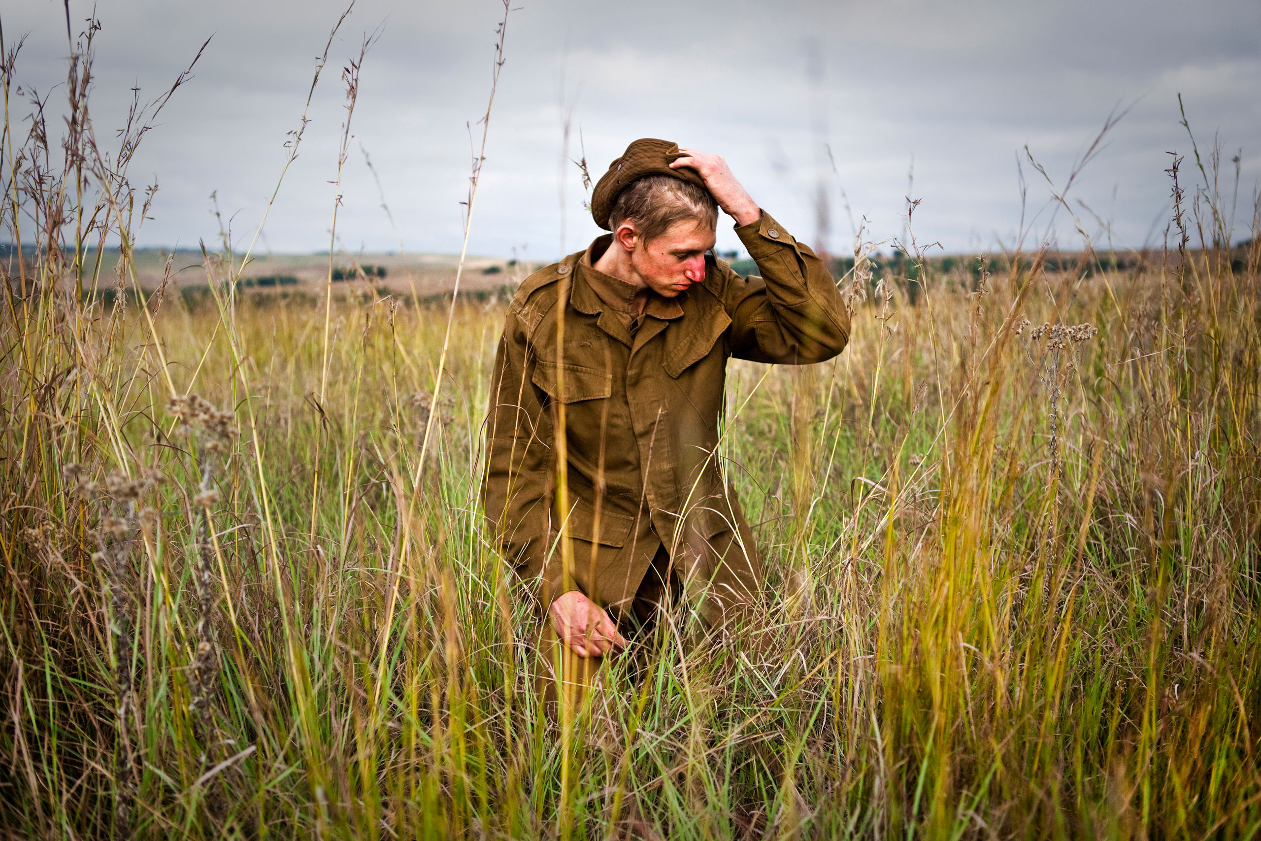 Riaan, one of the boys sits on his knees in a field at the end of an exercise.