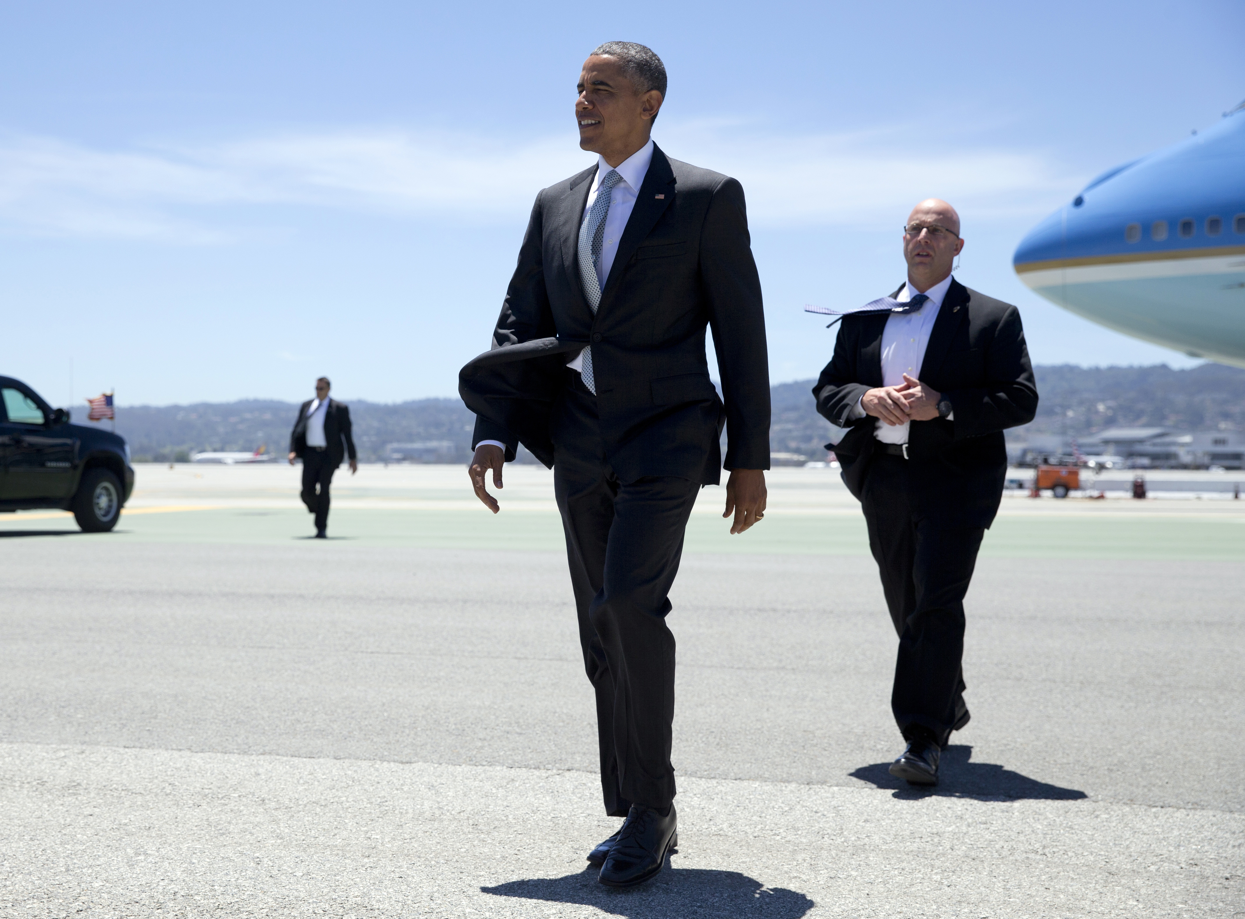 President Barack Obama walks across the tarmac to greet people as he arrives on Air Force One at San Francisco International airport June 19, 2015.