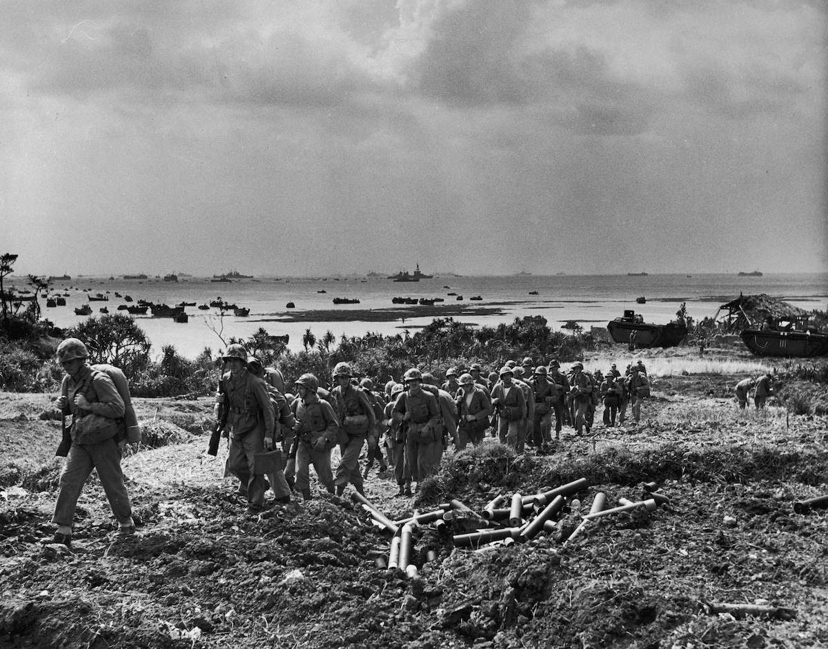 Soldiers of US 10th Army march inland after securing beachheads following the last amphibious assault landings of WWII as vessels from the Allied fleet patrol the waters off of Okinawa, Japan, April 1945.