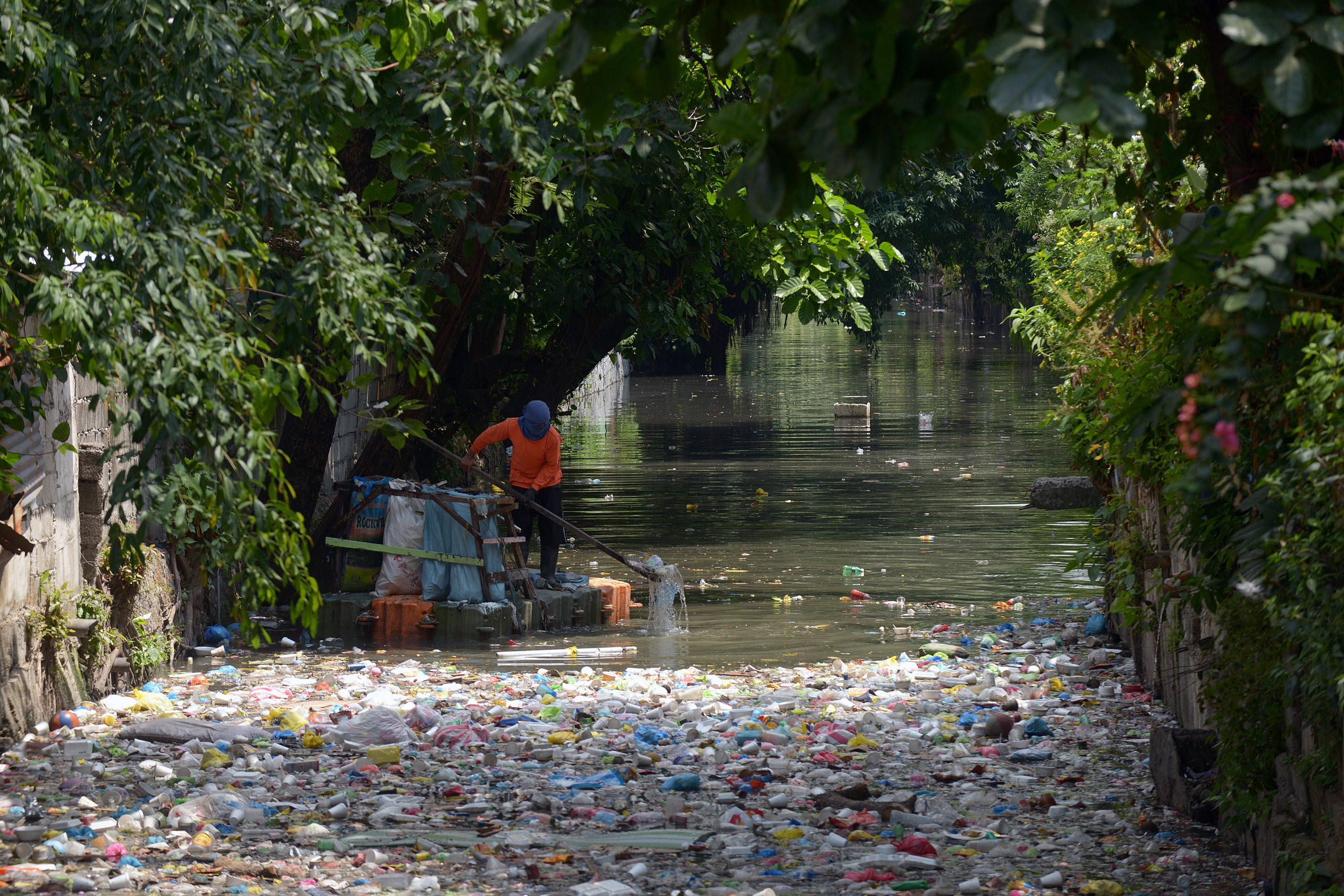 A cleanup volunteer scoops plastic waste at an open sewer in Manila on May 4, 2015. Nongovernmental environmental groups are calling for national legislation to prevent plastic waste that clog waterways