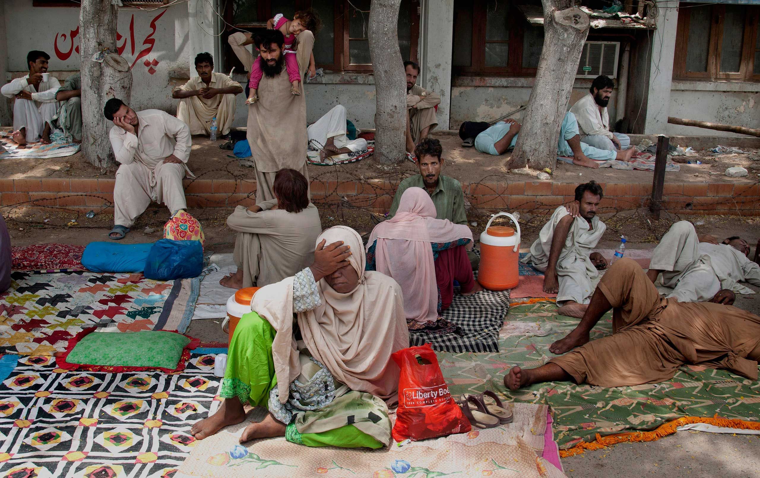 Relatives of patients suffering from heatstrokes take shelter under trees at a local hospital in Karachi, Pakistan, on June 24, 2015.