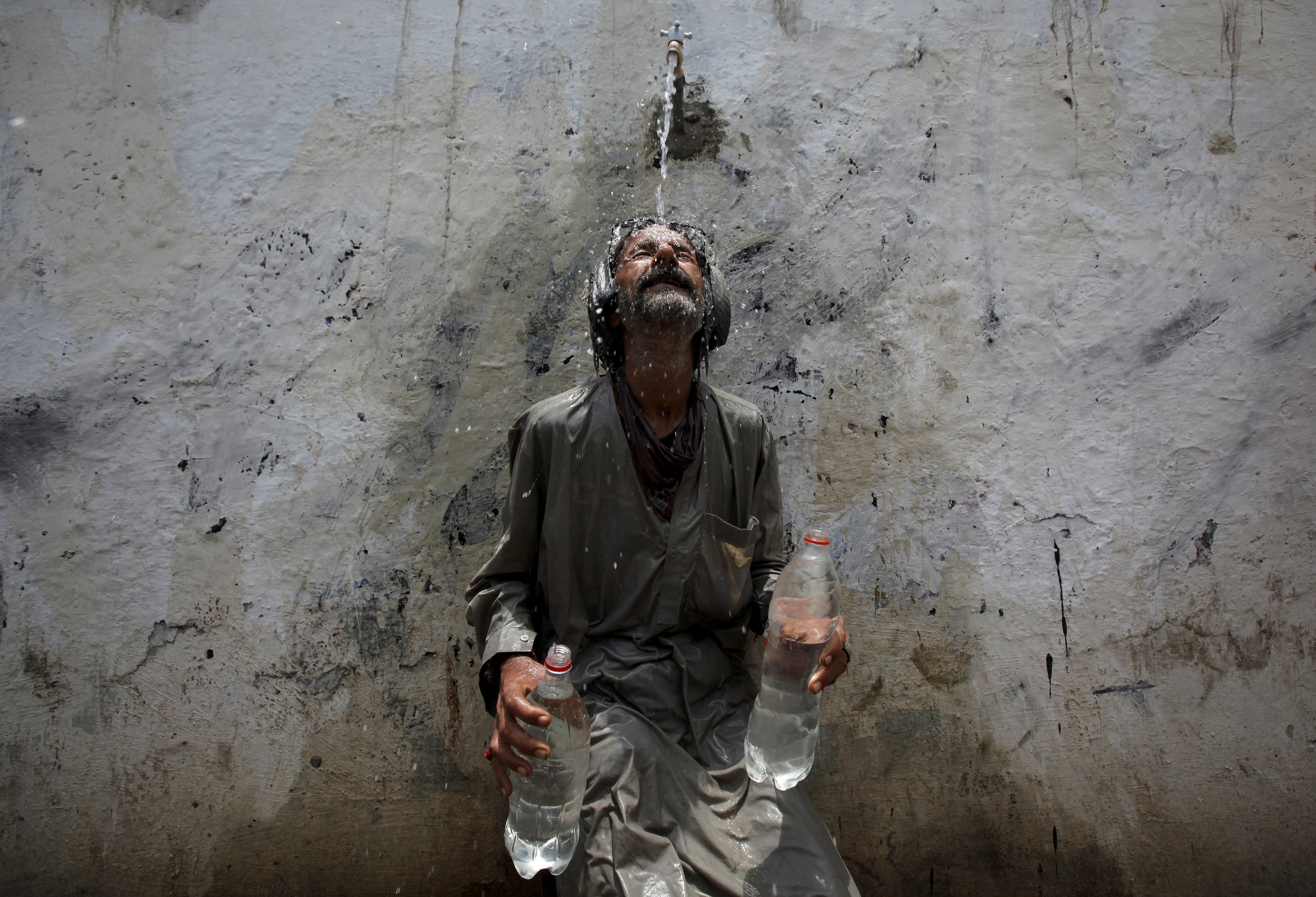 A man cools off from a public tap after filling bottles during intense hot weather in Karachi, Pakistan, on June 23, 2015.
