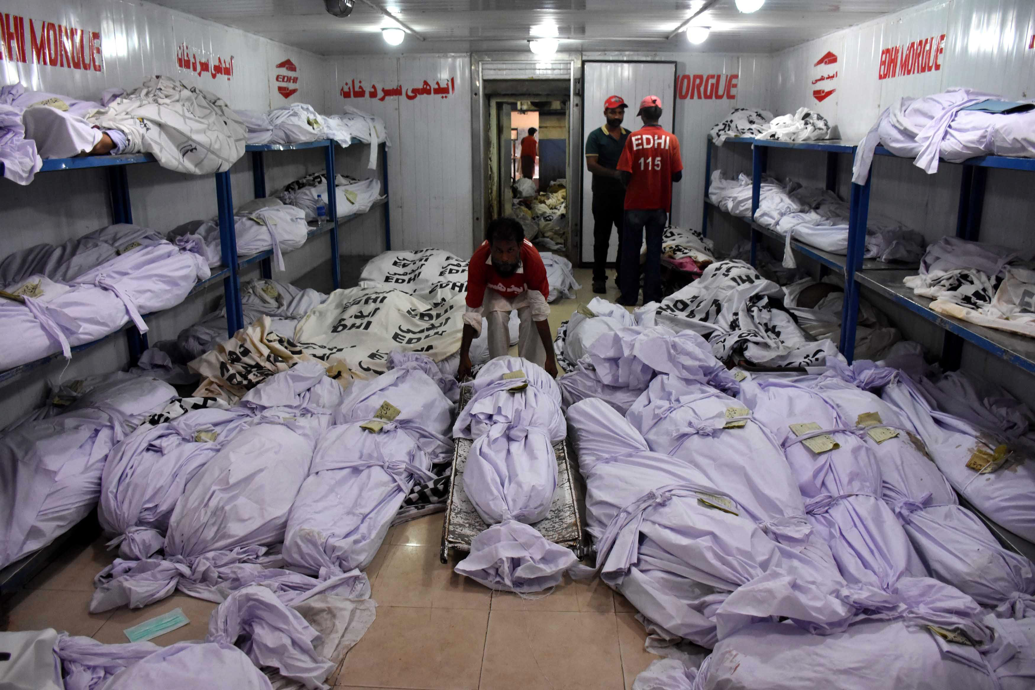 Rescue workers move the bodies of the victims of heat wave at a mortuary in Karachi, Pakistan, on June 22, 2015.