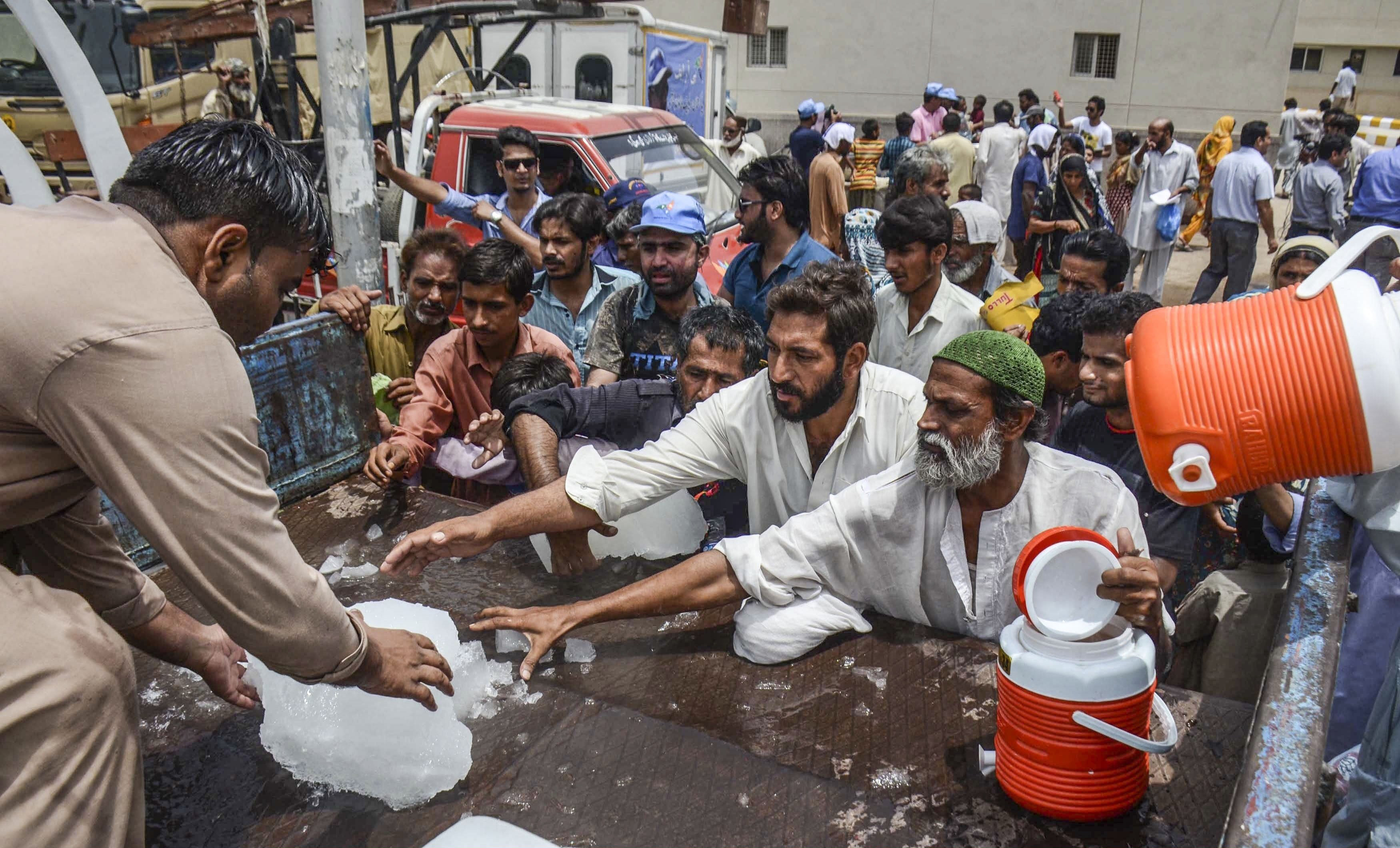 Pakistanis receive ice outside a hospital during a heat wave in Karachi, Pakistan, on June 24, 2015.