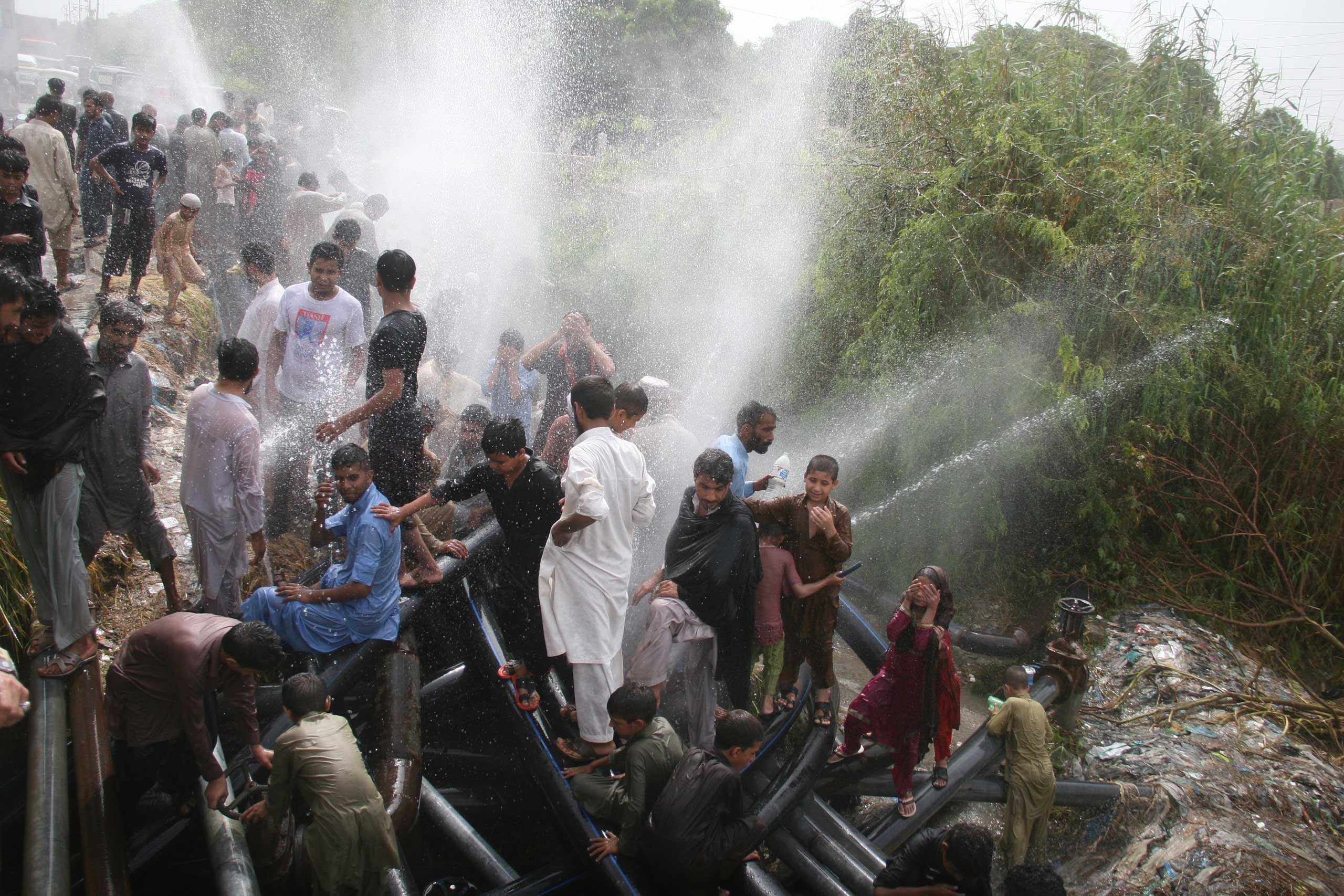 People cool off at water supply pipelines during a heat wave in Karachi, Pakistan, on June 24, 2015.
