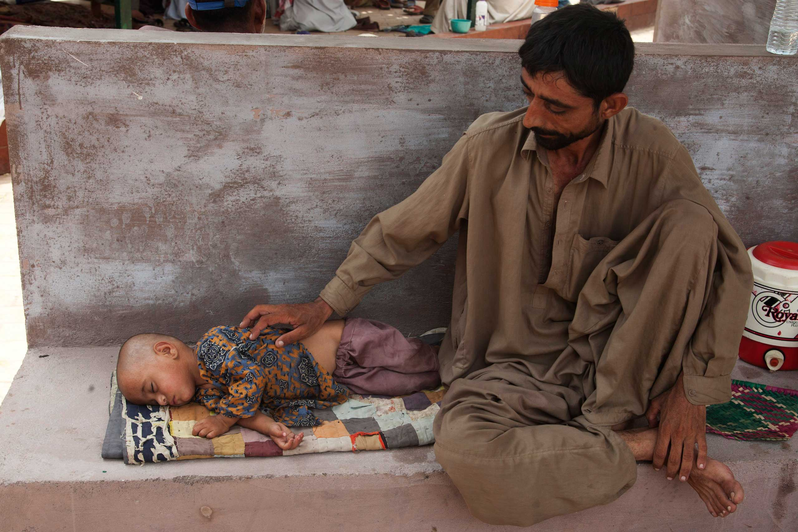 A man with his daughter who suffers from dehydration due to extreme weather waits for a medical help outside a ward at a child hospital in Karachi, Pakistan, on June 24, 2015.