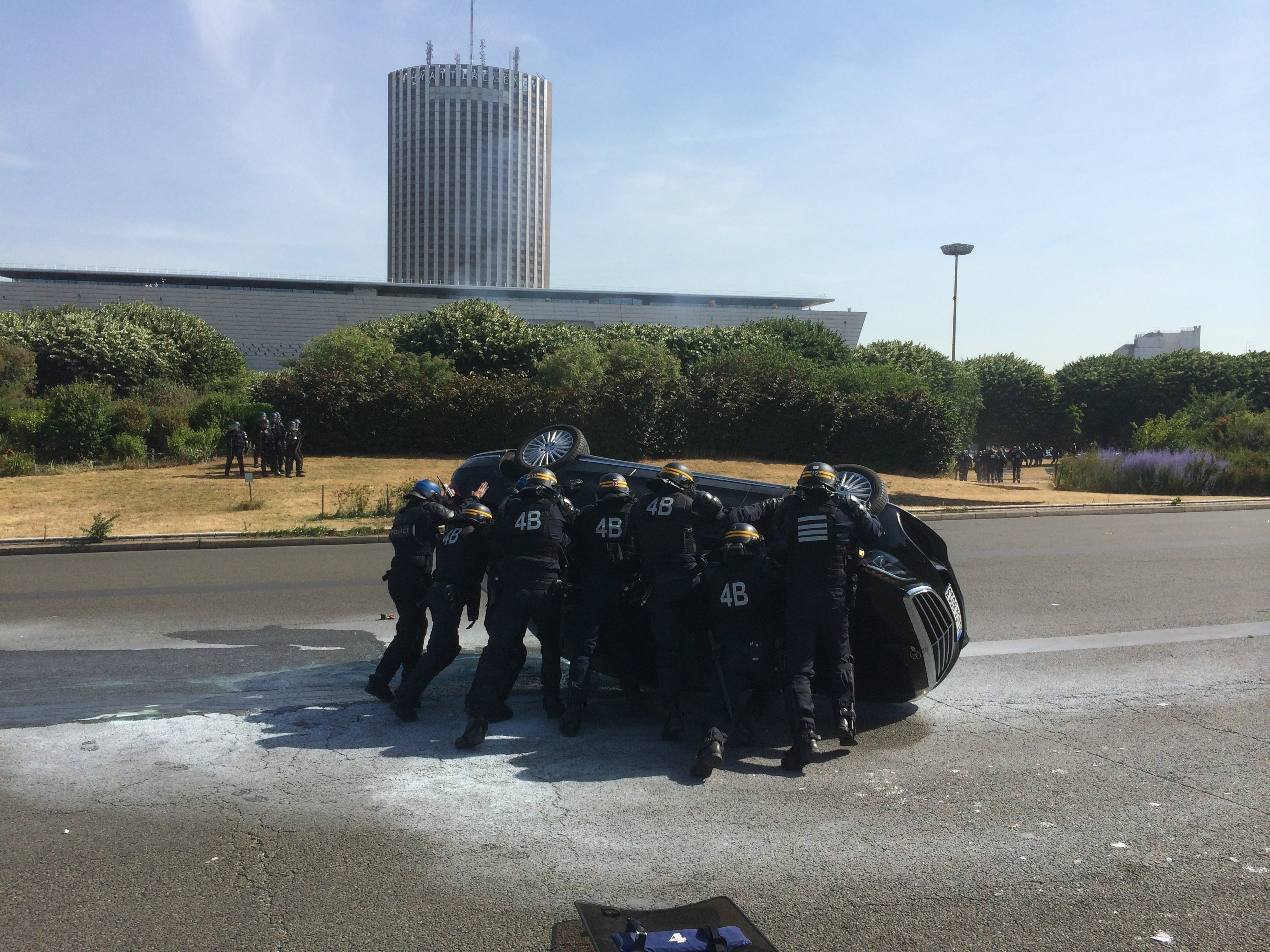 Police officers in riot gear attempt to flip a car back onto it's wheels at Porte Maillot on June 25, 2015 in Paris. Protesters blocked roads to airports and train stations, overturning cars and setting tires on fire.