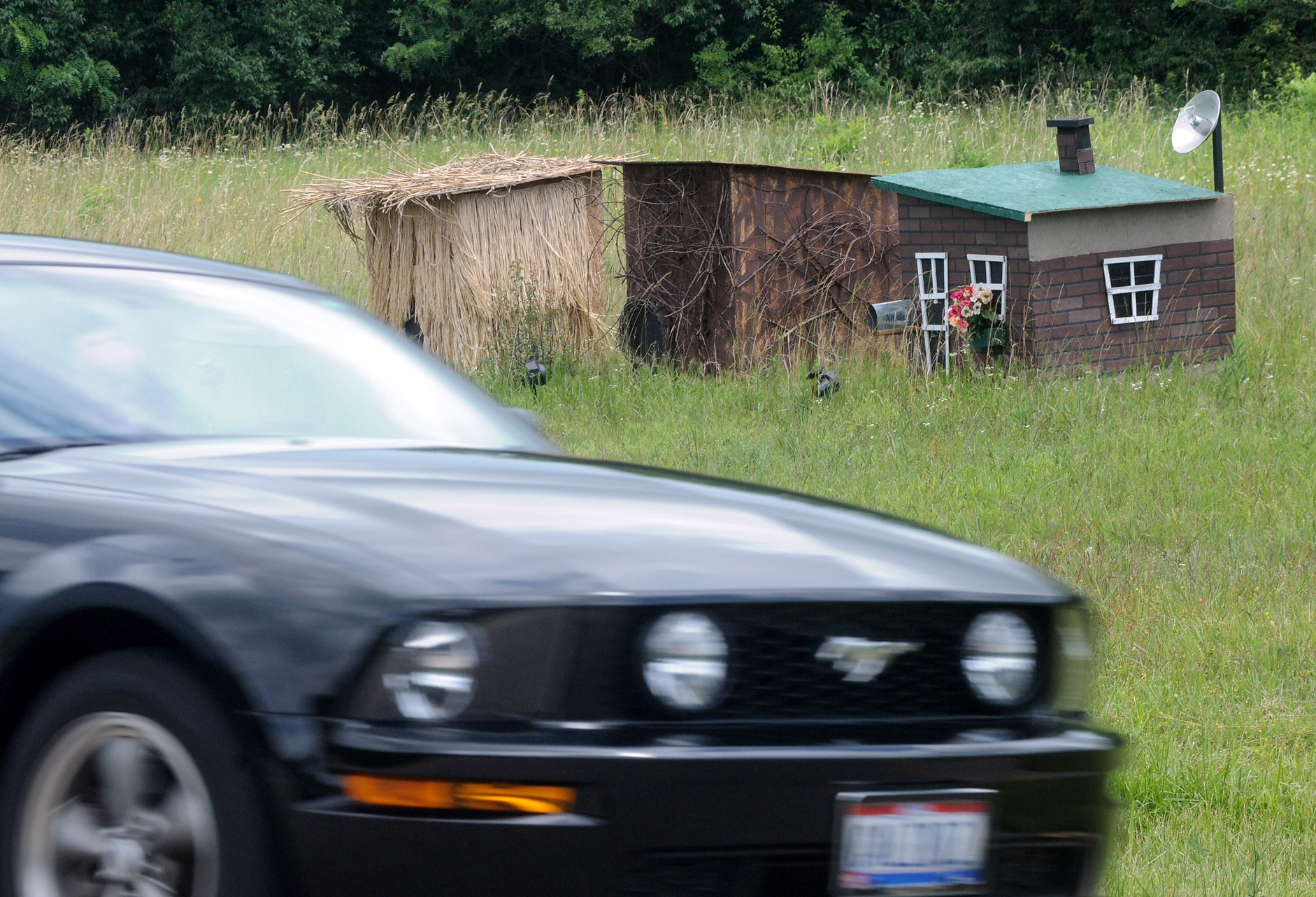 Three houses, one made of hay, one of sticks and one of bricks, have been constructed along U.S. Route 35 in Xenia Township west of Dayton, Ohio on June 15, 2015.