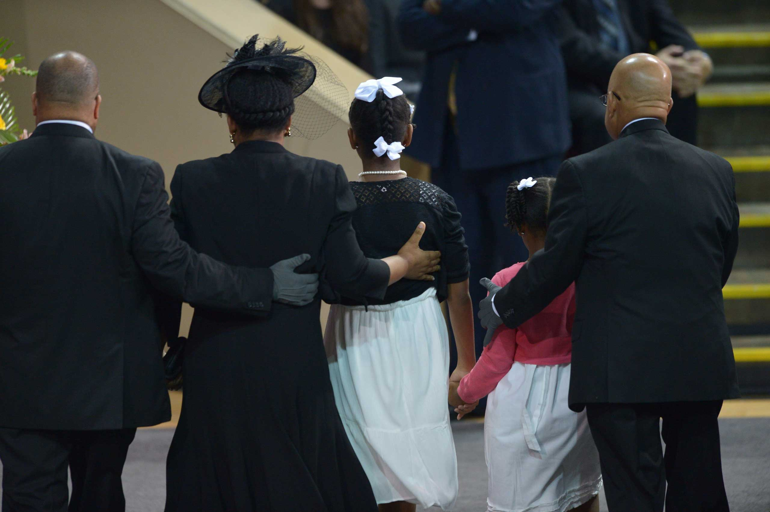 The wife of Rev. Clementa Pickney, Jennifer, stands with their daughters Malana  and Eliana before President Barack Obama delivers the eulogy during the funeral of Clementa Pickney, at the College of Charleston TD Arena, in Charleston, S.C. on June 26, 2015.