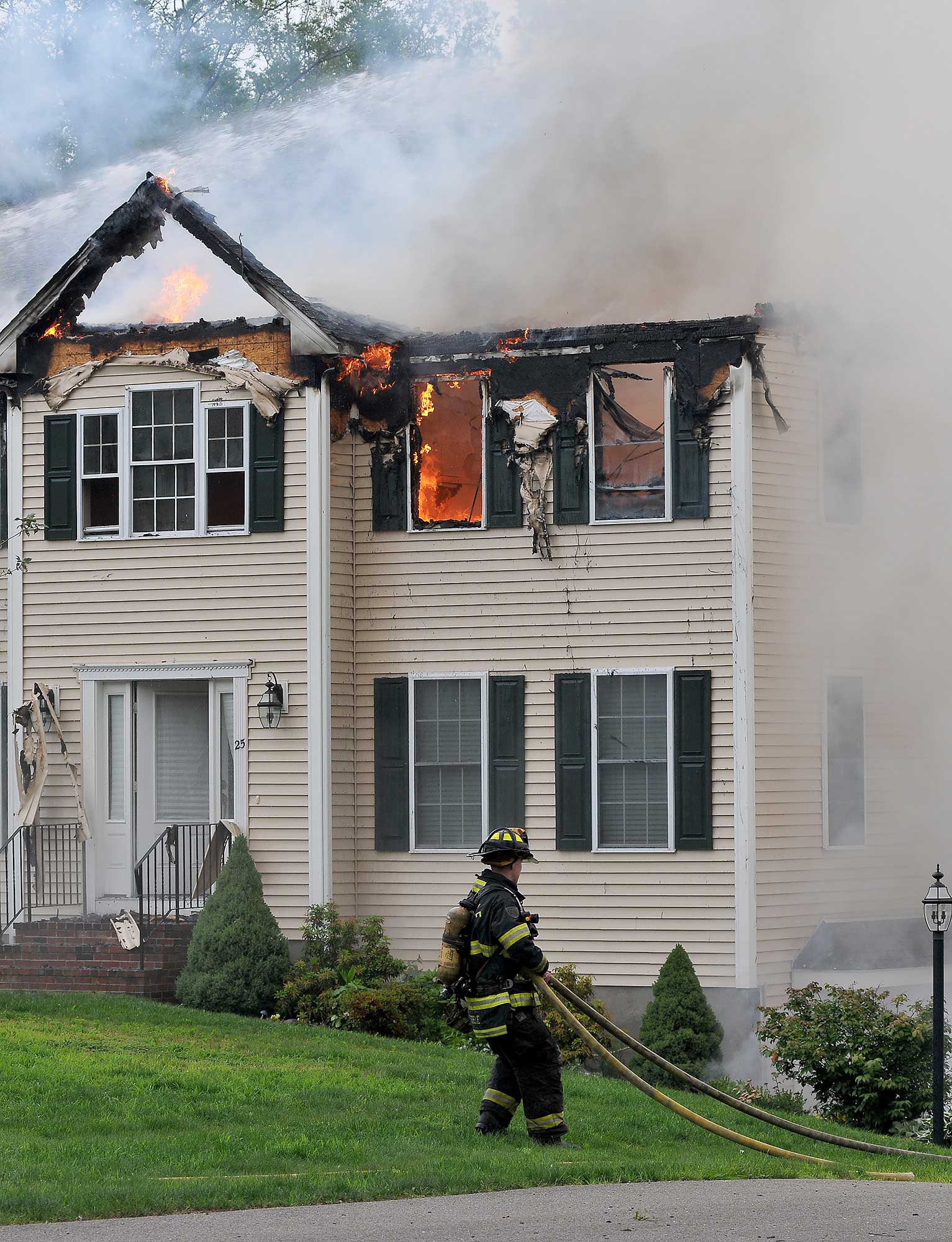 A firefighter moves a hose into position outside a house into which a small plane had crashed in Plainville, Mass., June 28, 2015.