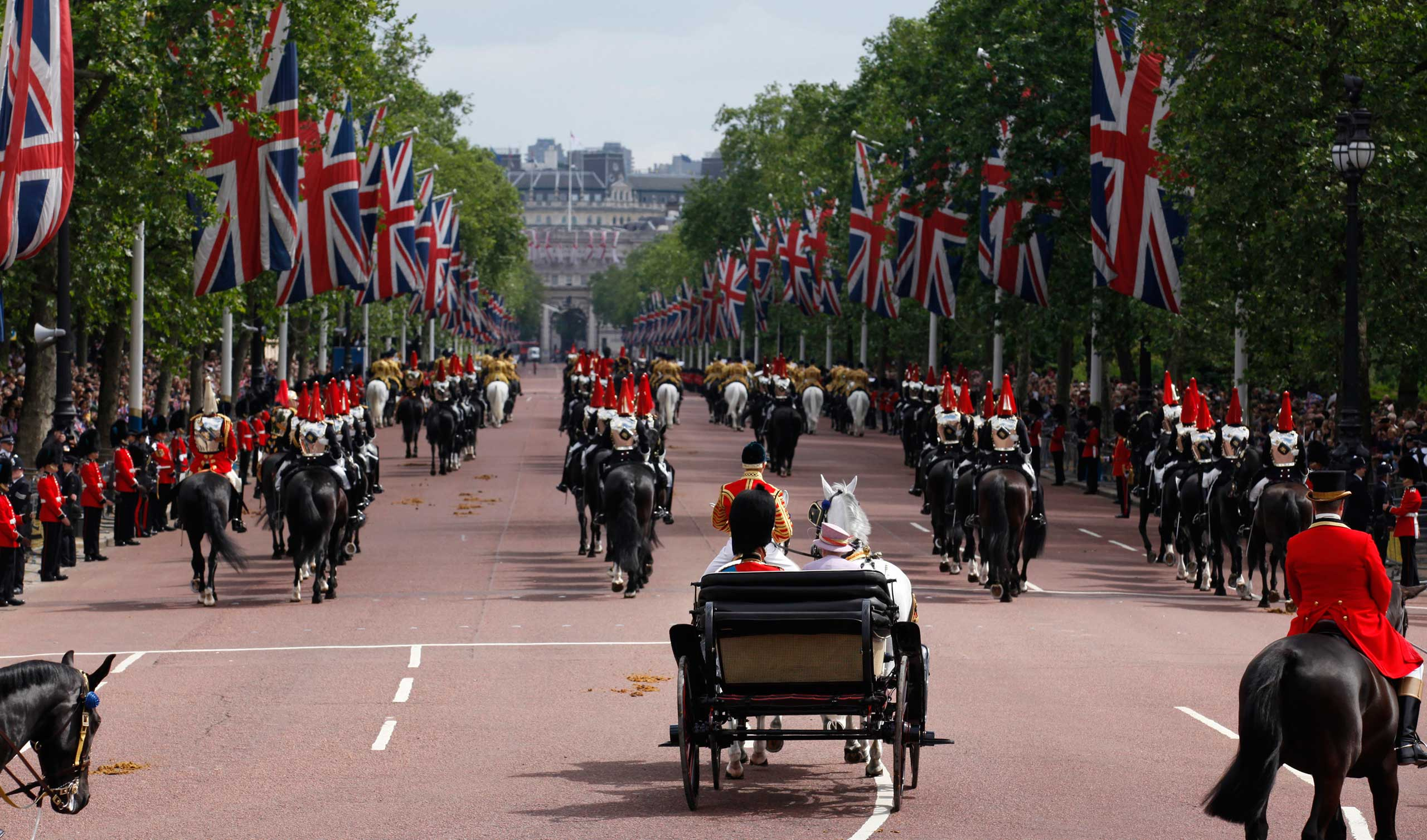 Queen Elizabeth II and Prince Philip leave Buckingham Palace to attend the Trooping the Colour ceremony in London to celebrate her official birthday in June 2010.