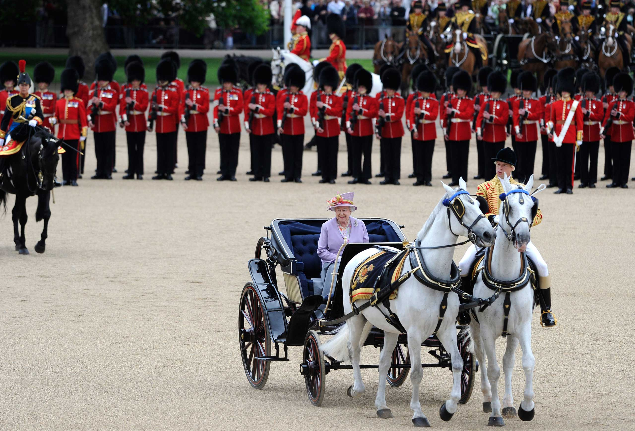 Queen Elizabeth II rides in an open carriage as she attends the Trooping the Colour ceremony to celebrate her official birthday in London in June 2010.