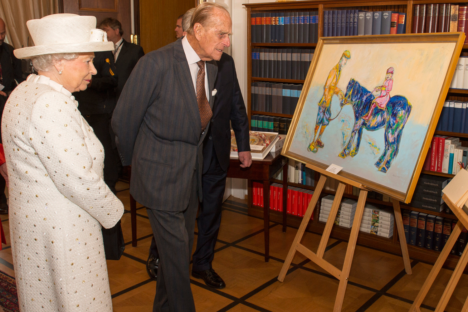 Britain's Queen Elizabeth and Prince Philip look at a painting presented to her during a visit to Germany's President's official residence, in Berlin, Germany, June 24, 2015.