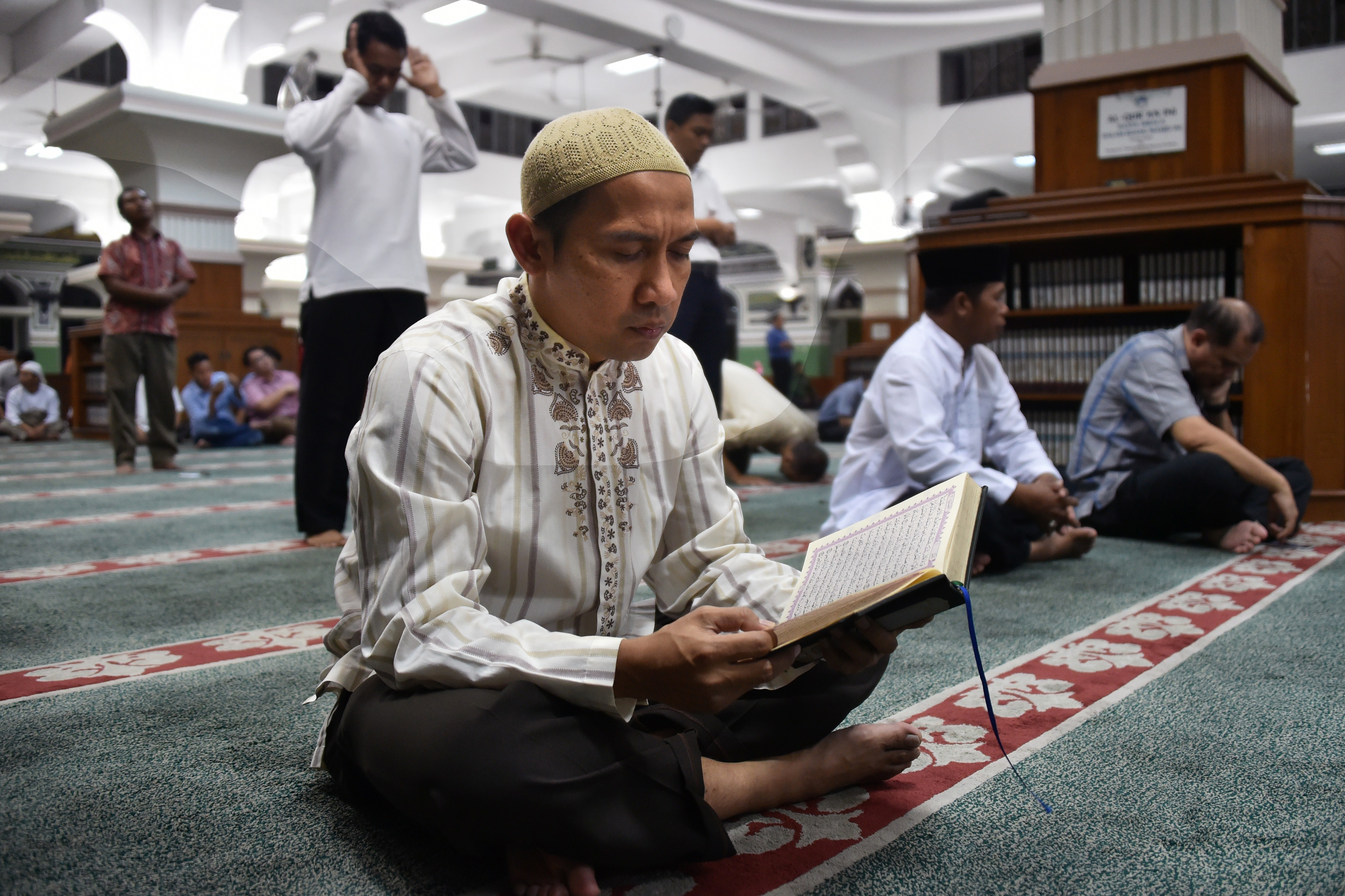 A man reads the koran as Indonesian Muslims wait for the first day of Ramadan prayers at Al-azhar Mosque in Jakarta on June 17, 2015, to mark the Muslim holy fasting month.