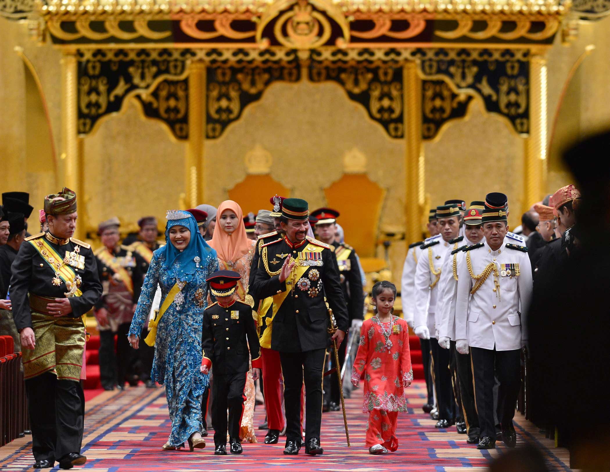 Bruneiís Sultan Hassanal Bolkiah and members of the royal family leave the throne room after his 67th birthday celebrations at Nurul Iman Palace in Bandar Seri Begawan on Sept. 15, 2013.