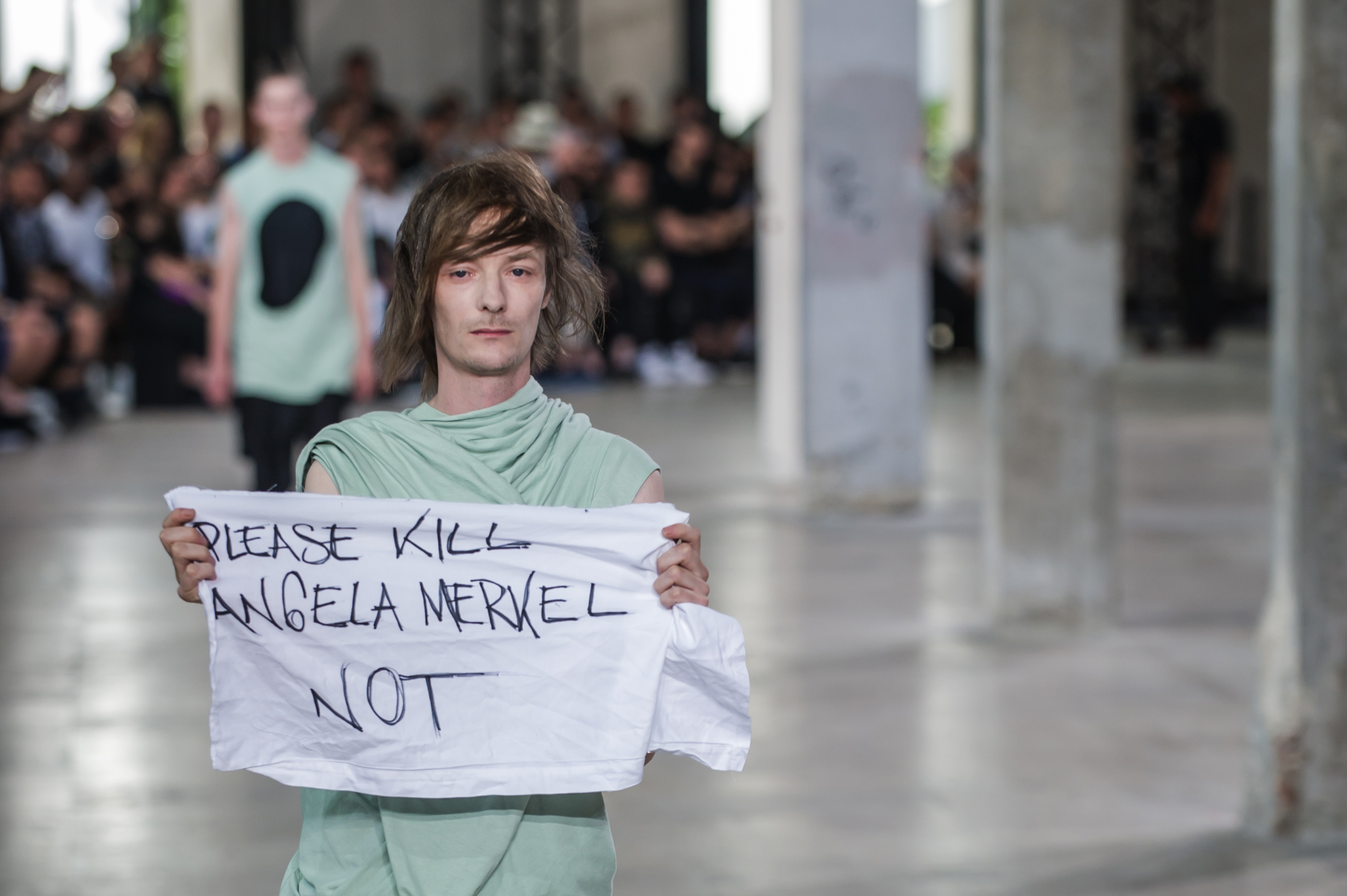 A model wears a creation by Rick Owens and holds a banner reading  Please kill Angela Merkel not , as part of his men's Spring/Summer 2016 collection presented in Paris, June 25, 2015.