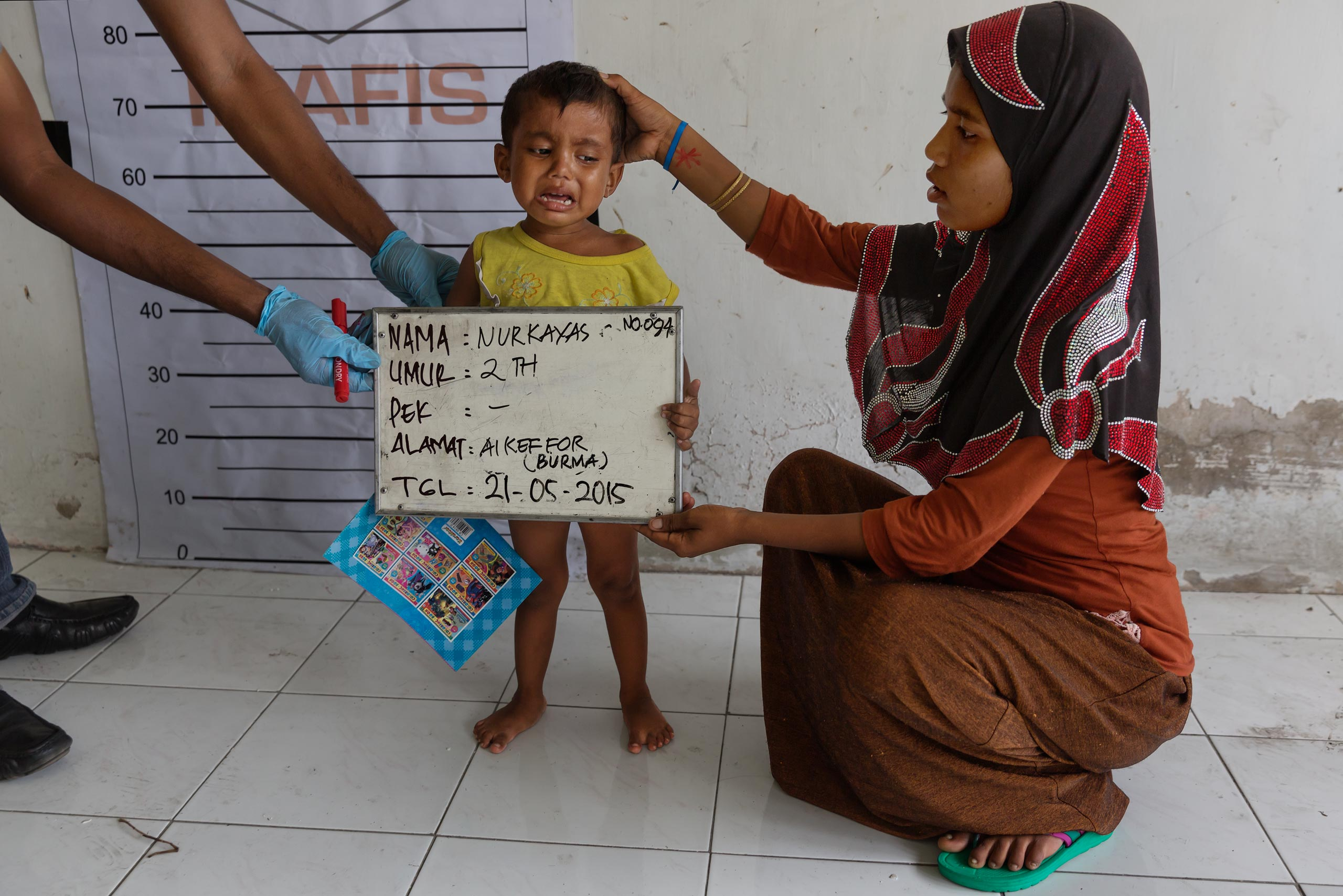 A 2-year-old boy cries as he is being registered at a temporary shelter in Indonesia.