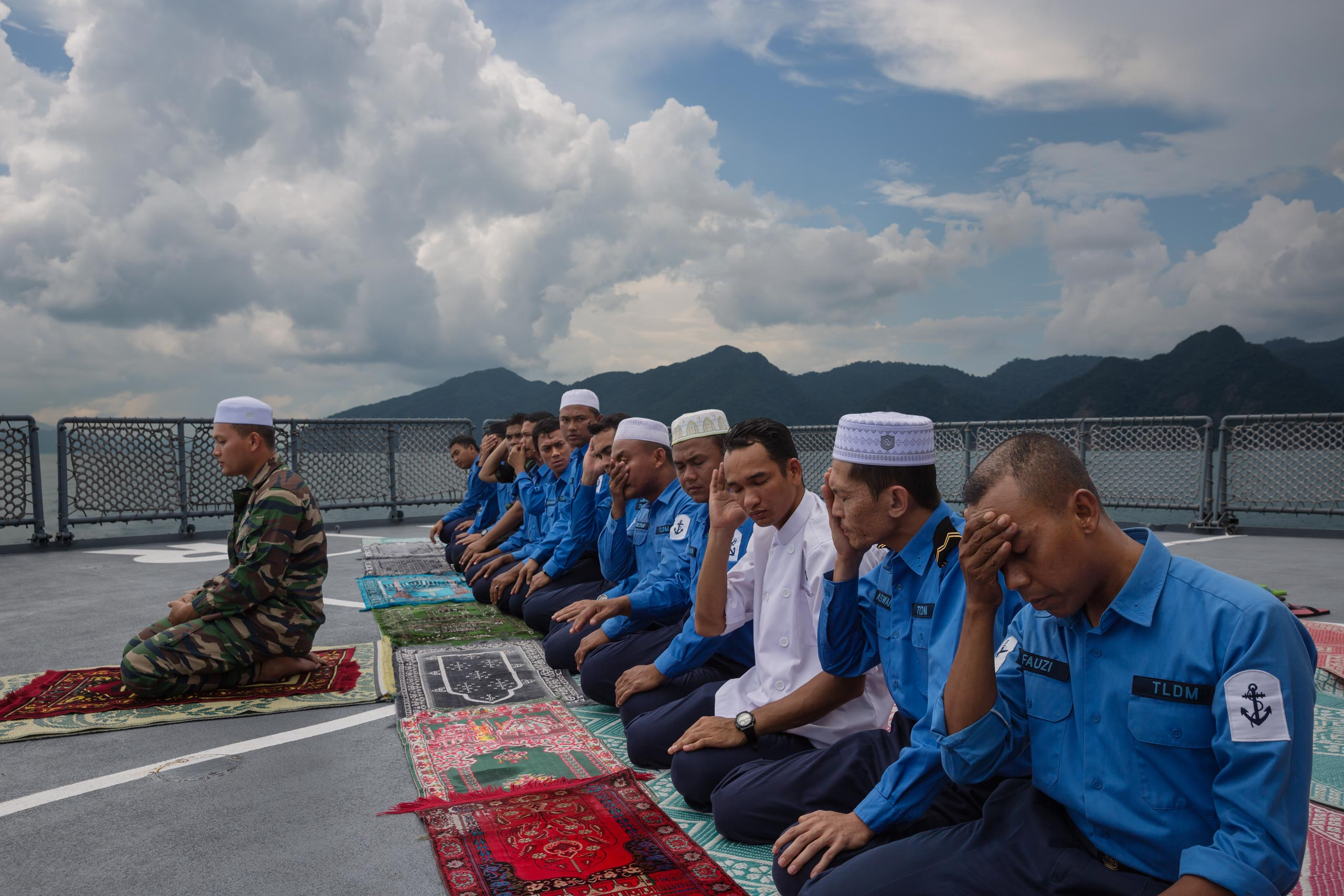 Malaysian Navy officers pray on a navy ship out of Langkawi, an island in the Andaman Sea. They are on routine patrol looking for boats with Rohingya refugees in waters neighboring Thailand.