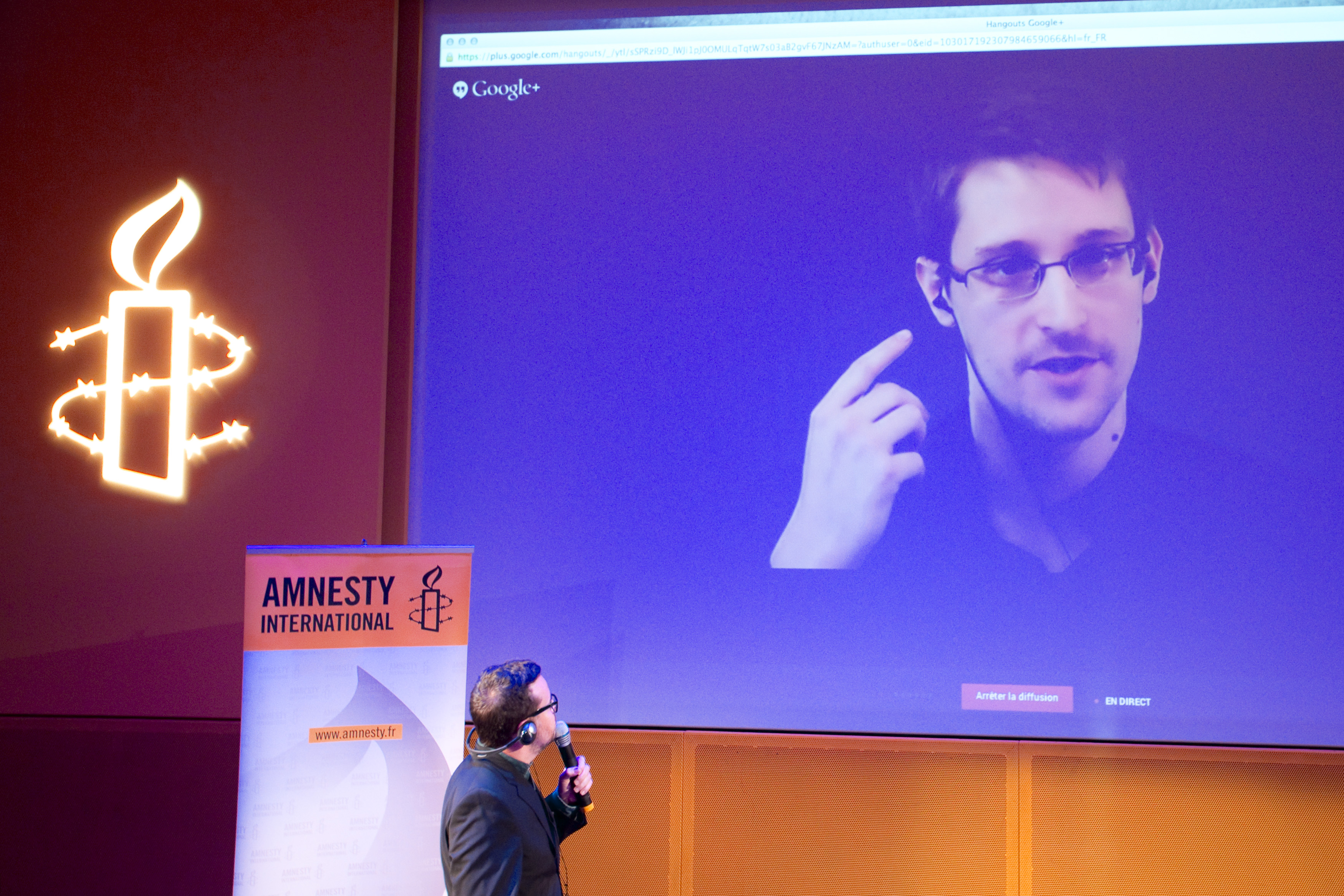 Former U.S. National Security Agency contractor Edward Snowden, who is in Moscow, is seen on a giant screen during a live video conference for an interview as part of Amnesty International's annual Write for Rights campaign at the Gaite Lyrique in Paris December 10, 2014