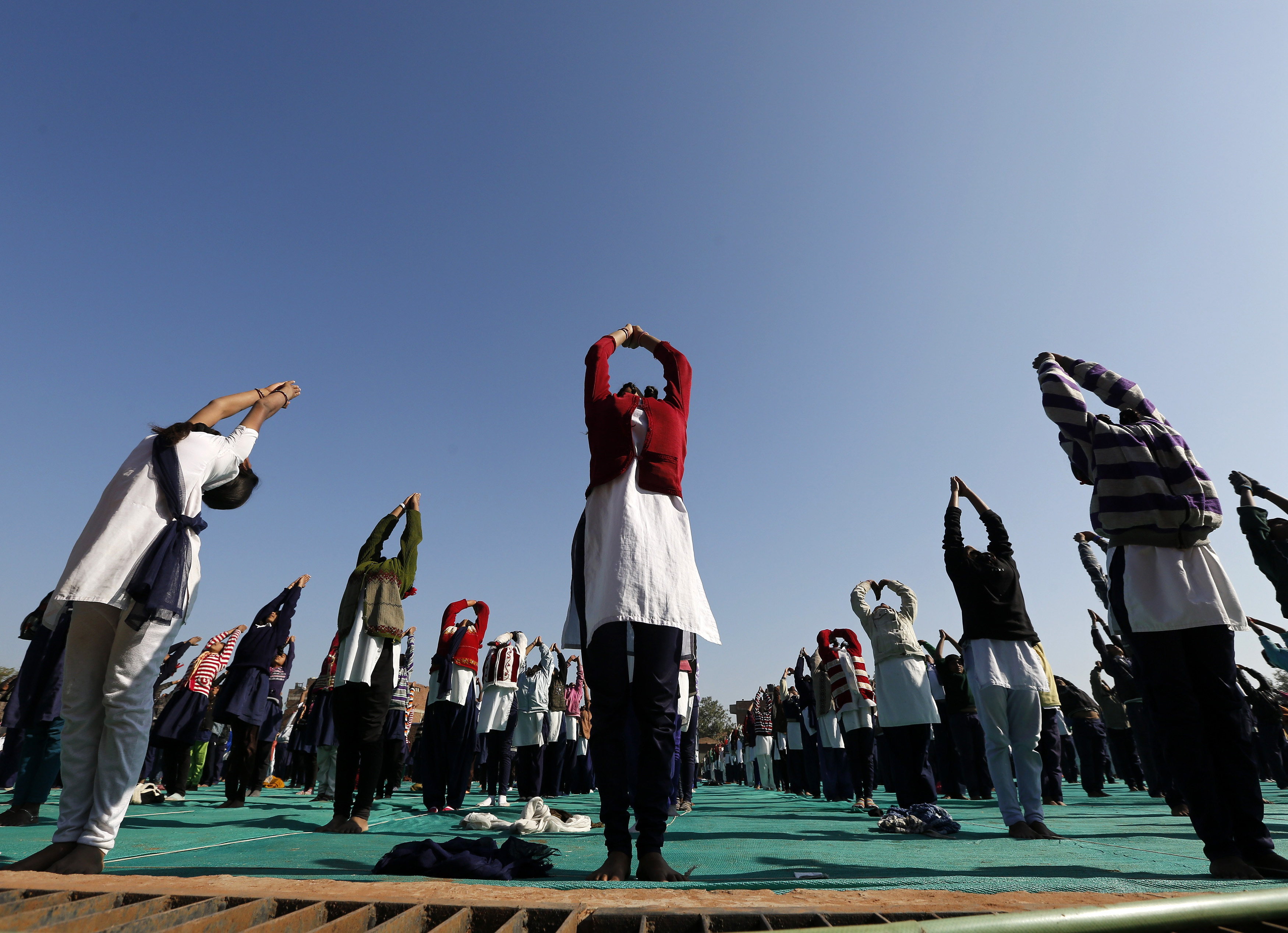 Schoolchildren offer prayers to the sun god during a yoga session at a camp in the western Indian city of Ahmedabad on Jan. 6, 2015