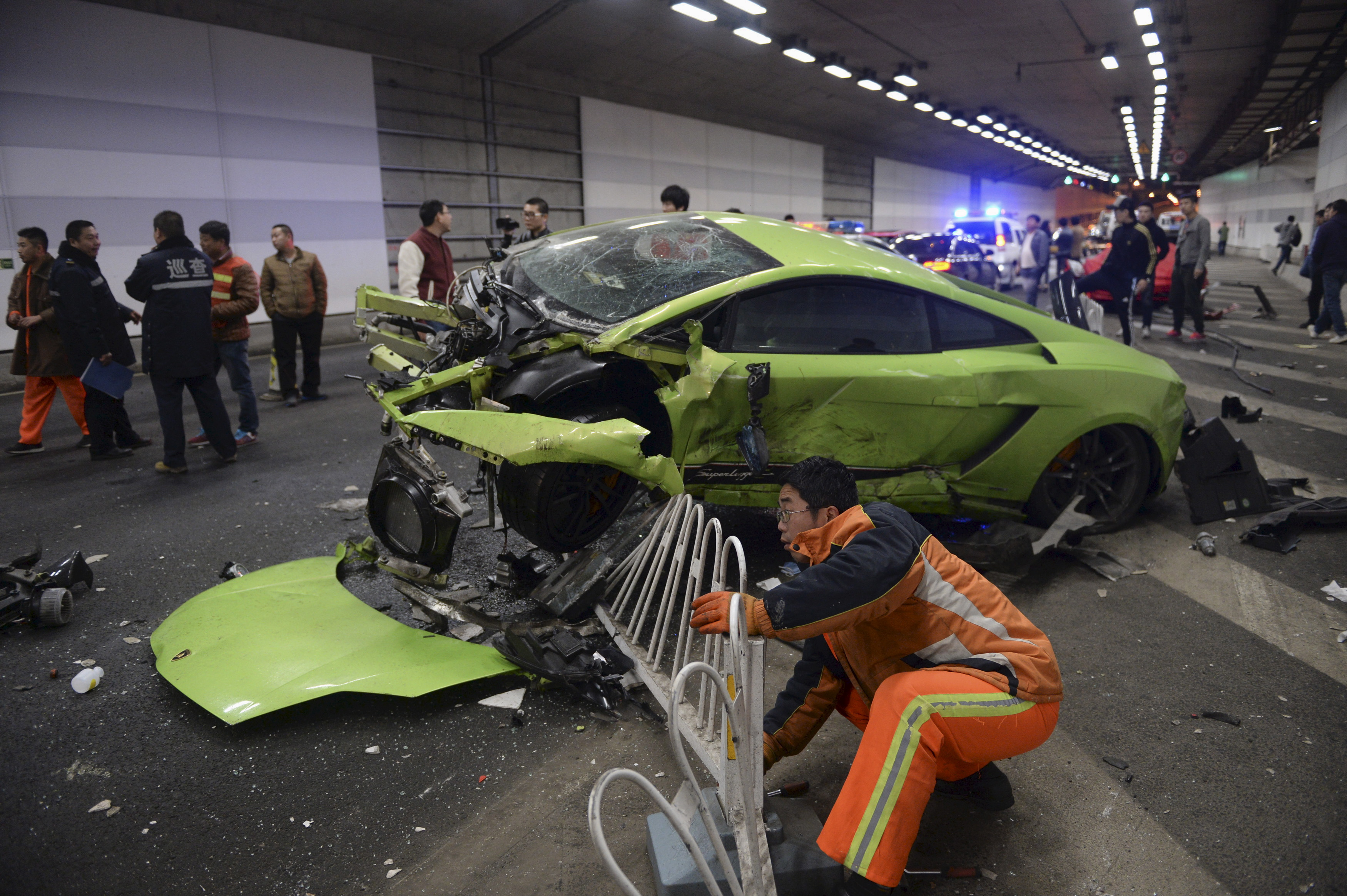 A rescuer tries to remove a part of a broken fence from a damaged Lamborghini that collided with a Ferrari inside a tunnel in Beijing on April 12, 2015